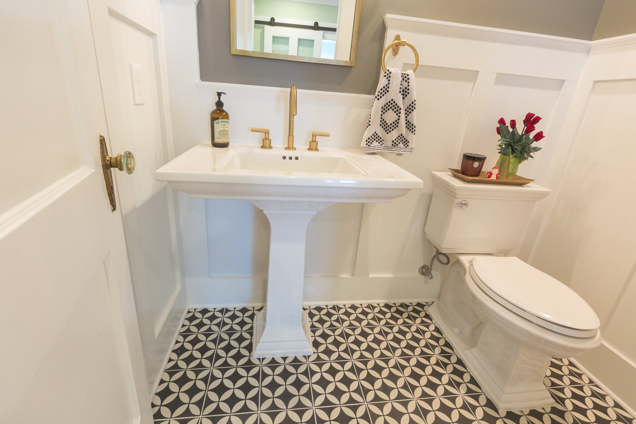 Vintage patterned tile makes this powder room seem larger. Perfectly paired with the pedestal sink and classic brass faucet.