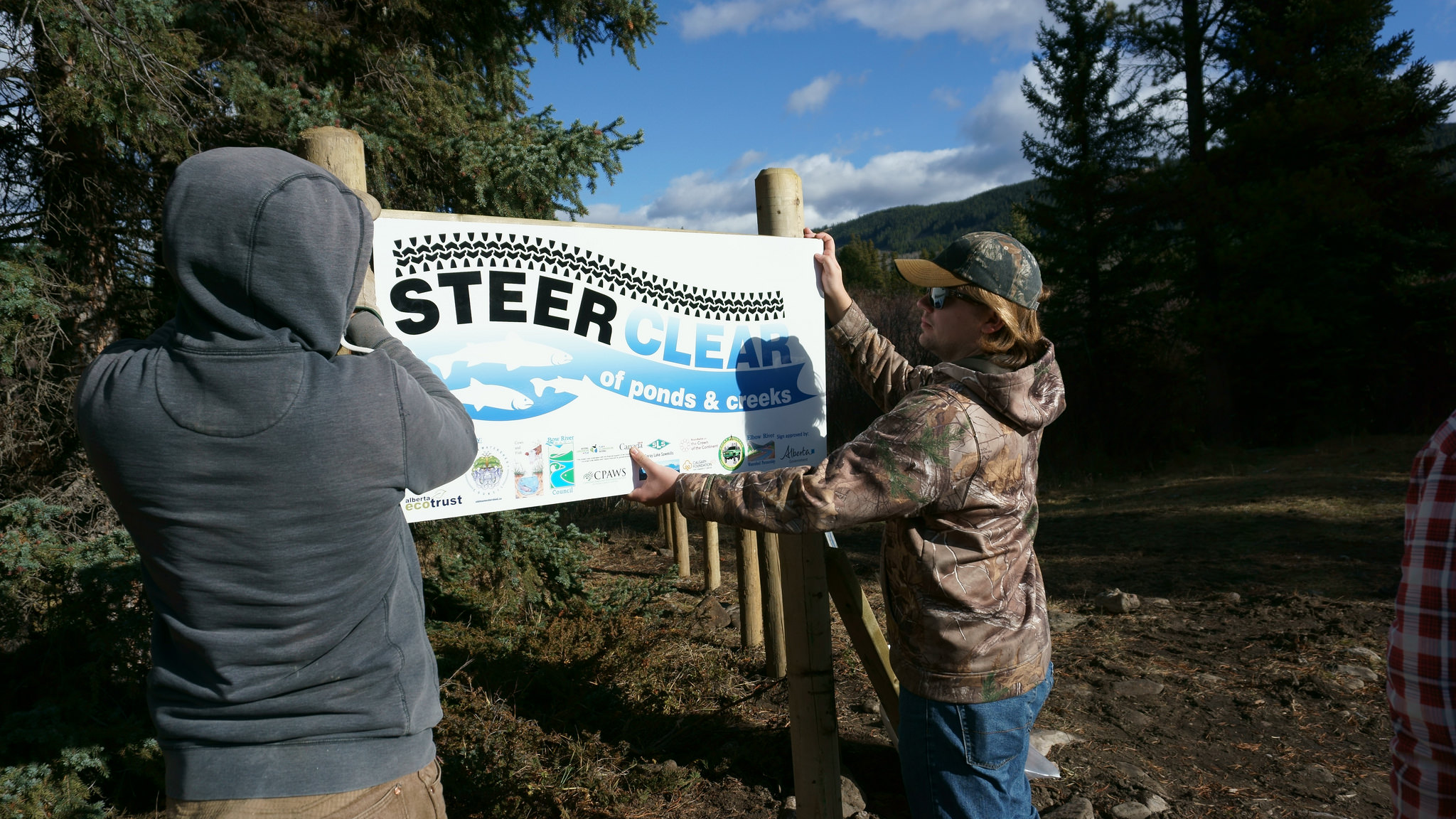 WLP Program Manager Cody Spencer (L) and volunteer Dylan Brassard put up one of 4 signs installed near the site. 2 are 'Steer Clear' signs and 2 explain the restoration activities.