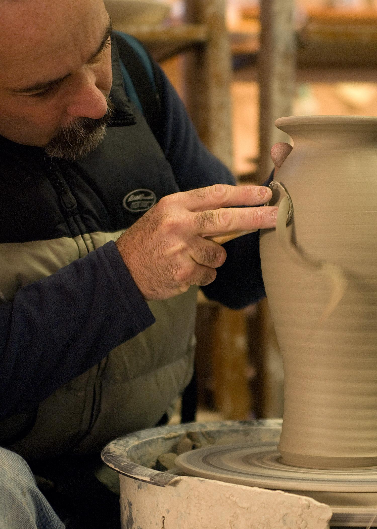 Putting finishing touches on a vase.