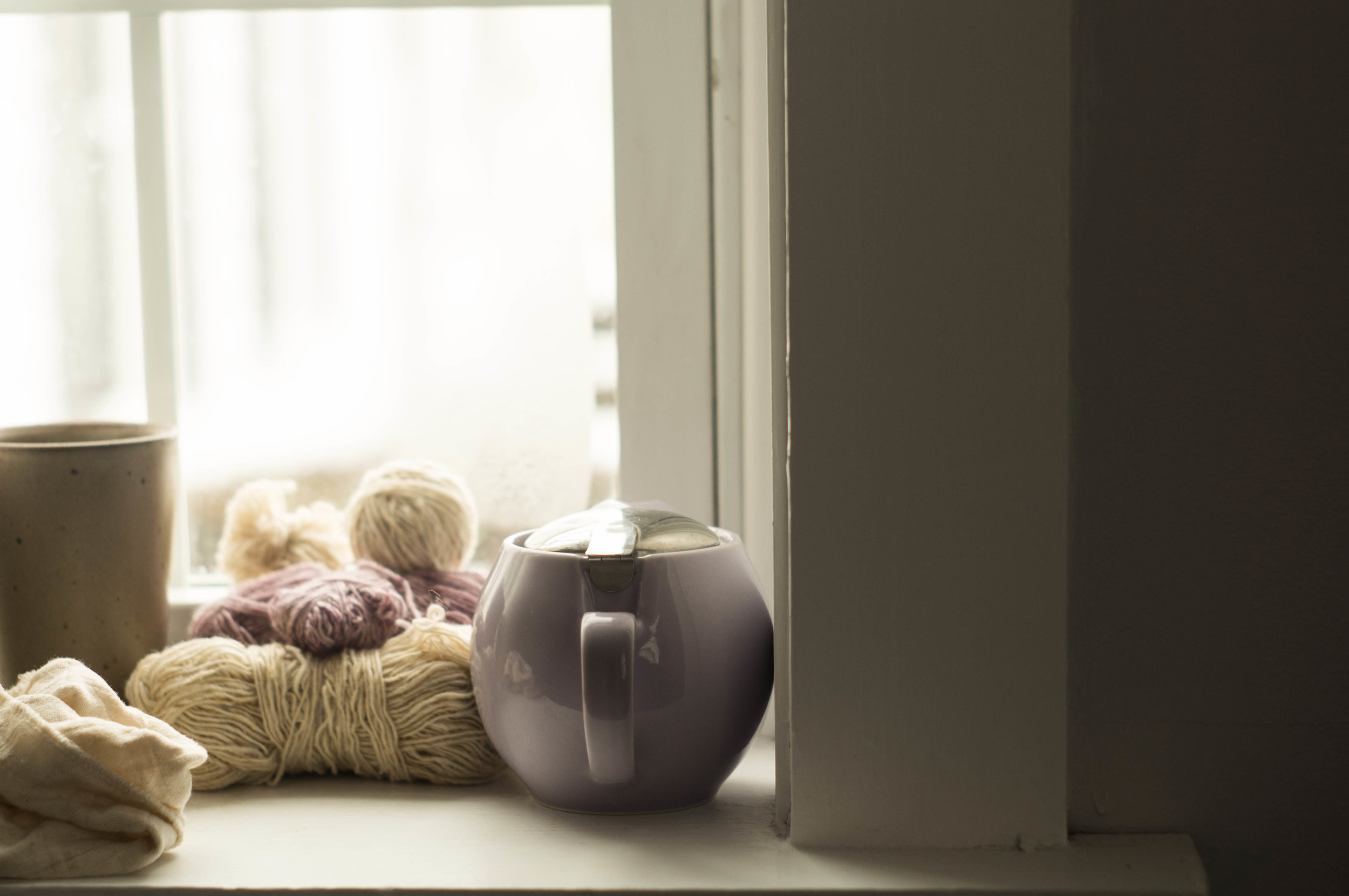 wool yarn and a tea kettle on a windowsill by samantha spigos