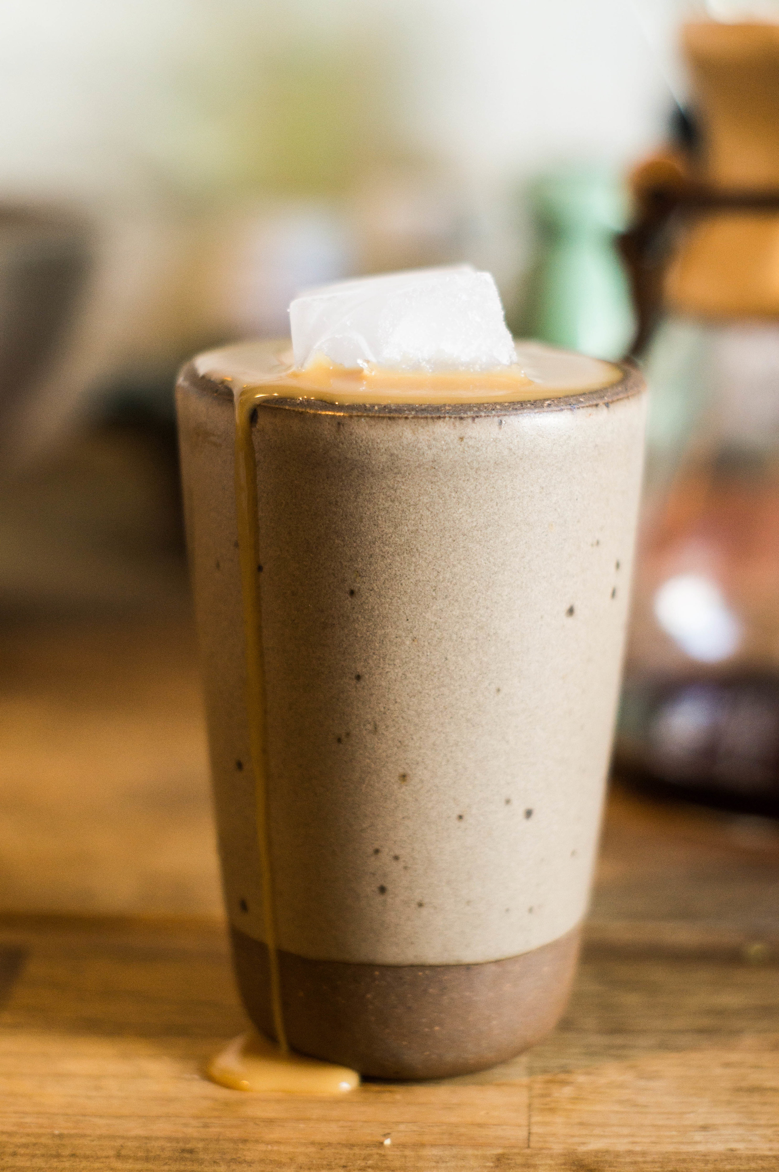 iced coffee with cream spilling over a stoneware cup by samantha spigos