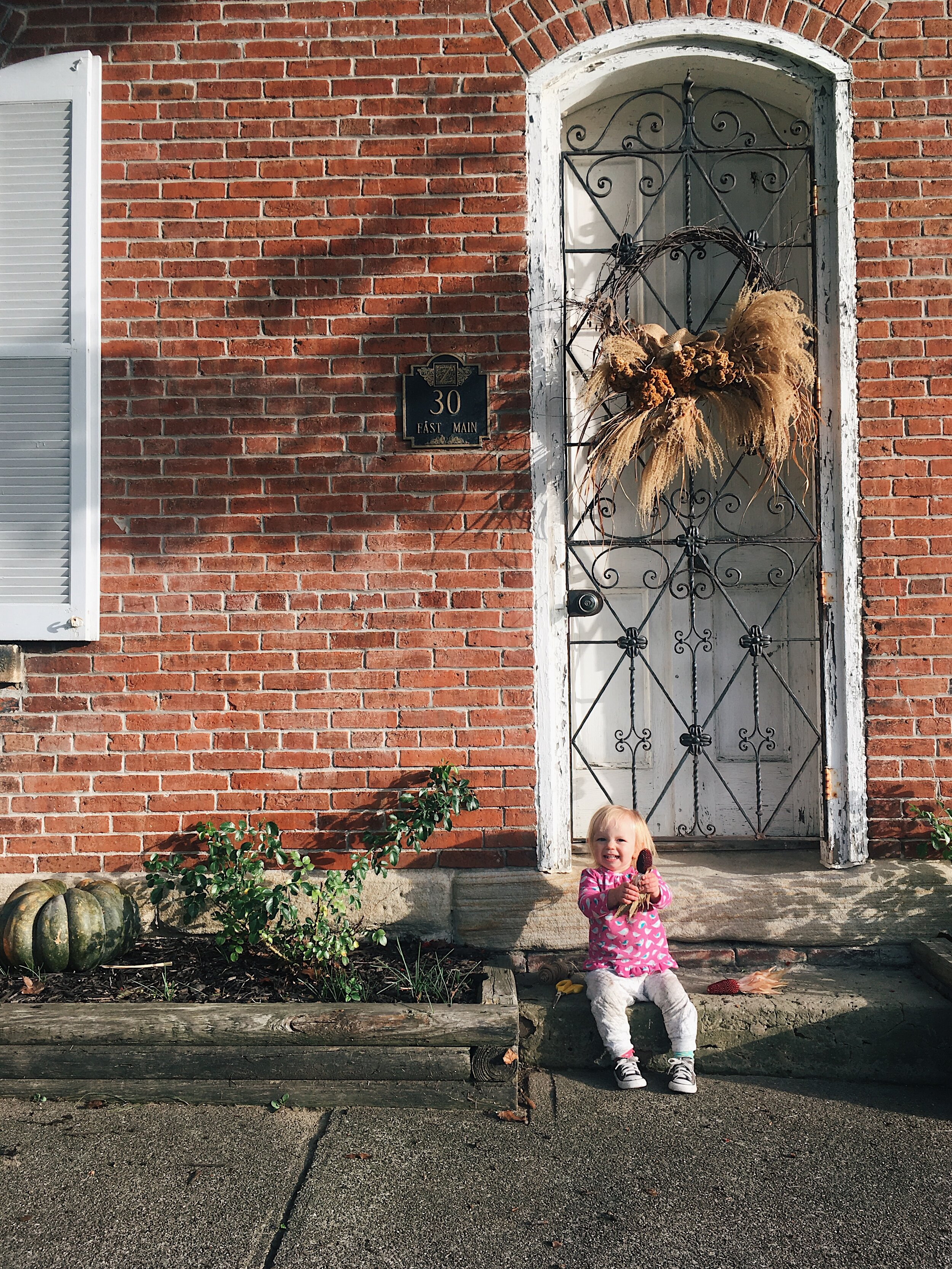 child in front of a brick house in autumn by samantha spigos