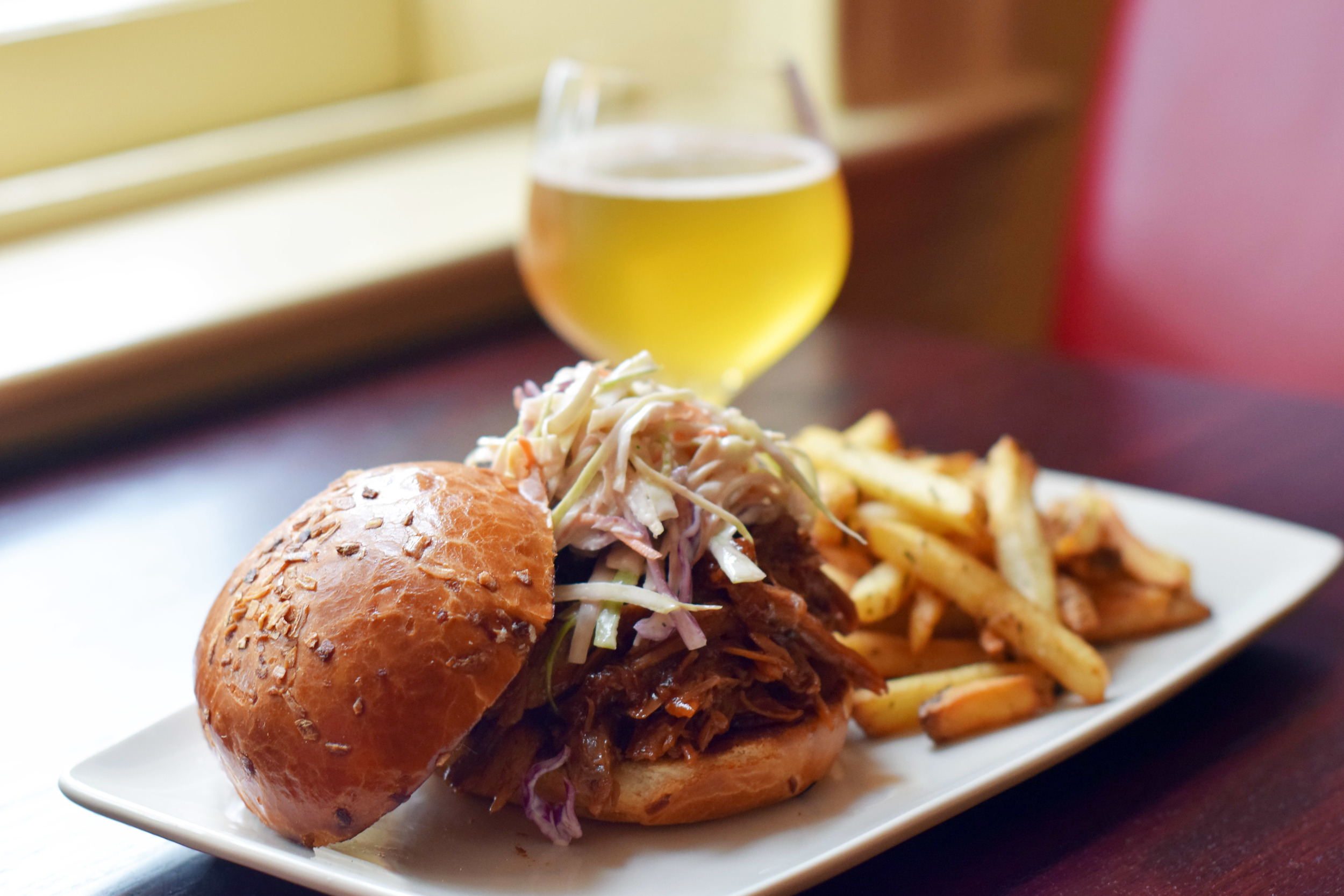 PULLED PORK SANDWICH house smoked pork, smoked apple BBQ, brioche bun, slaw, garlic confit & rosemary fries