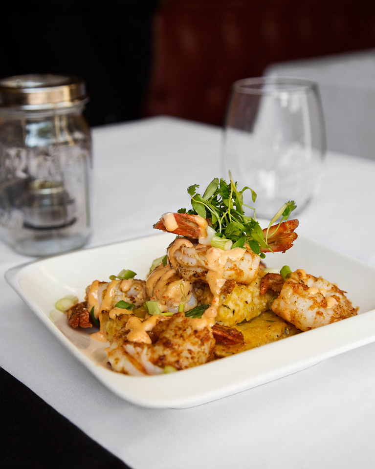 MAGNOLIA'S SHRIMP and GRITS jumbo gulf shrimp, chipotle cheddar grit cake, red pepper aioli, scallion