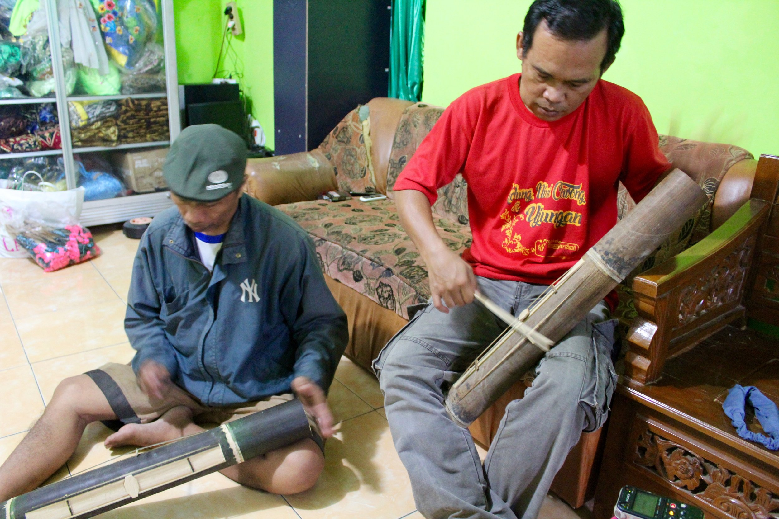 Pak Pakel (left) and Pak Yusmanto (right) jam out in the living room. Pakel's gumbeng is a little bit green as it hasn't been properly dried yet.