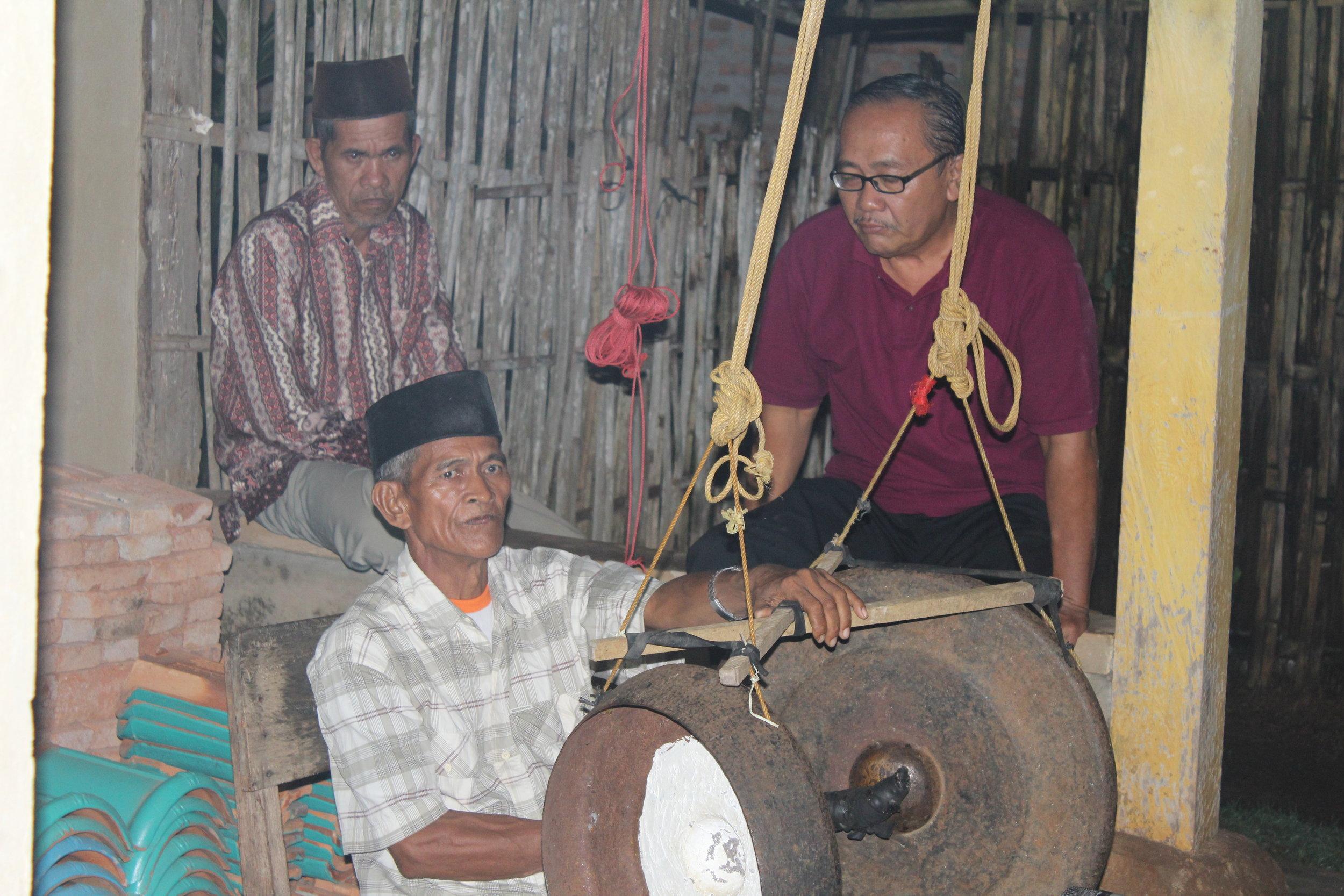Pak Budiman Yakub (Raden Kesuma Yudha, right) watches as Pak Umar (Ngegugo) plays  gung  in Peniangan.