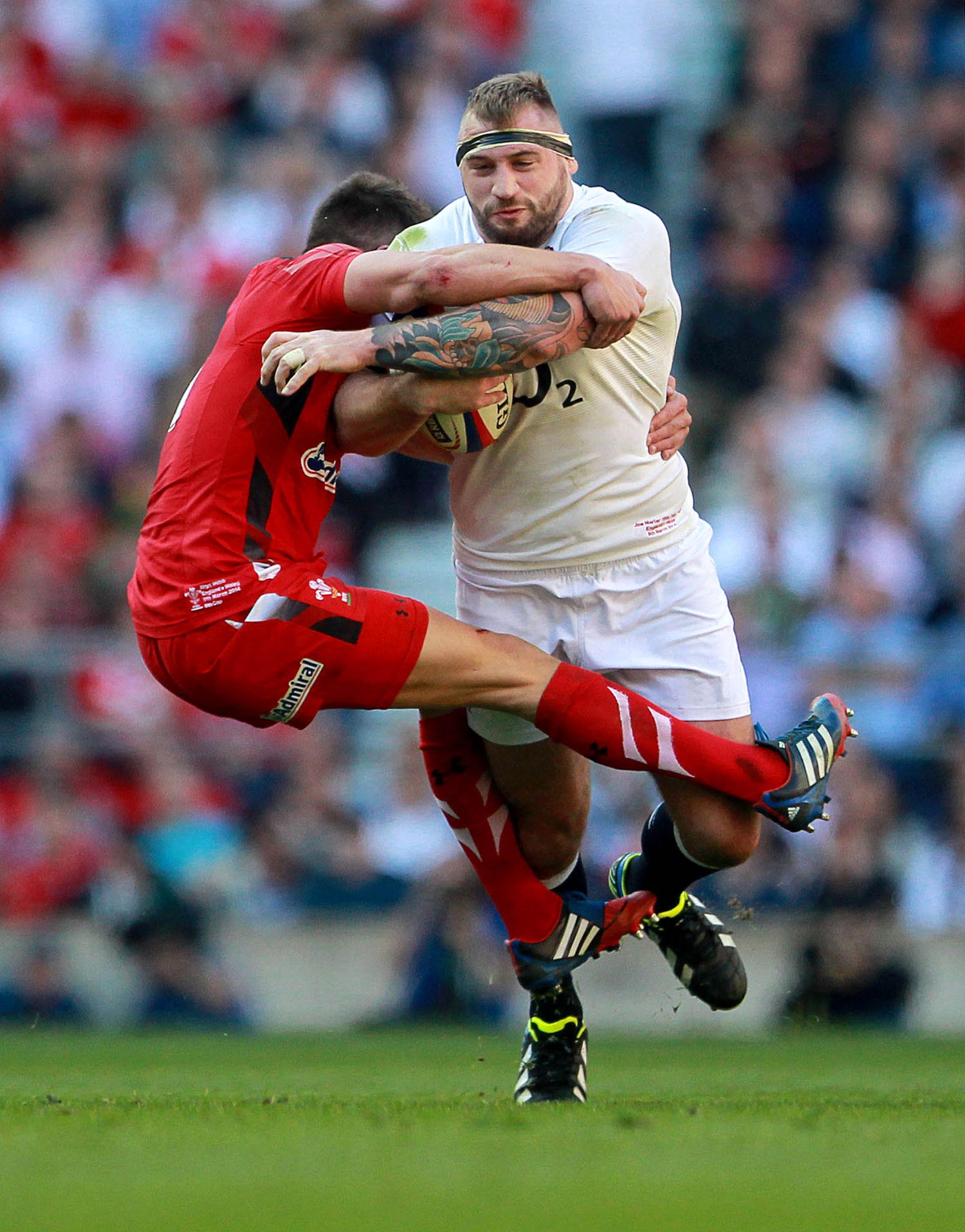 Joe Marler of England is tackled by Rhys Webb of Wales