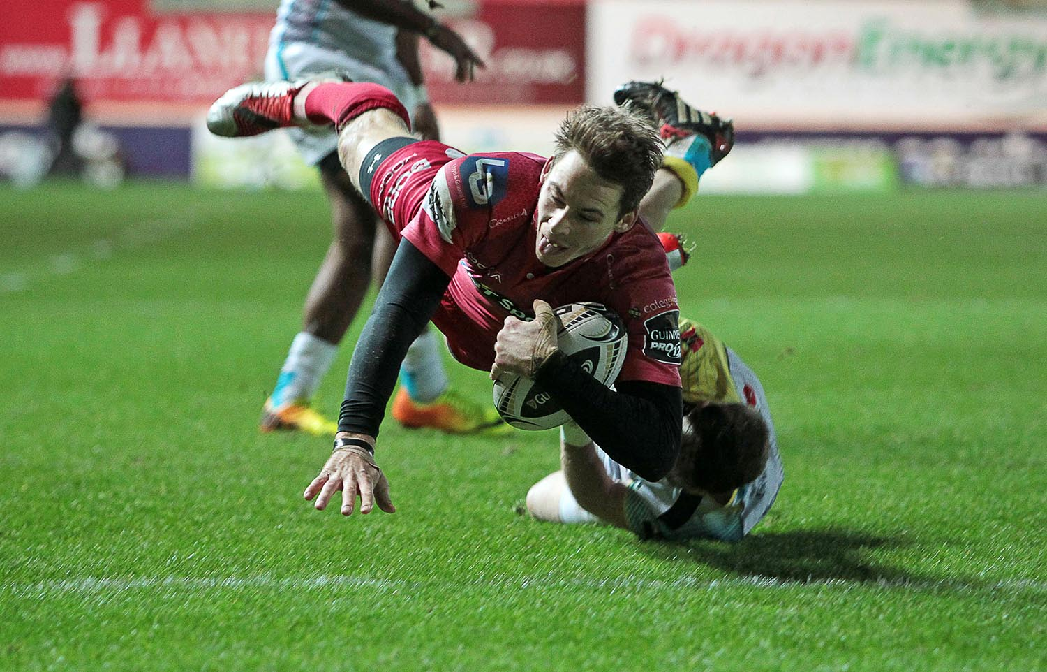 Liam Williams of Scarlets beats Martin Roberts of Ospreys to score