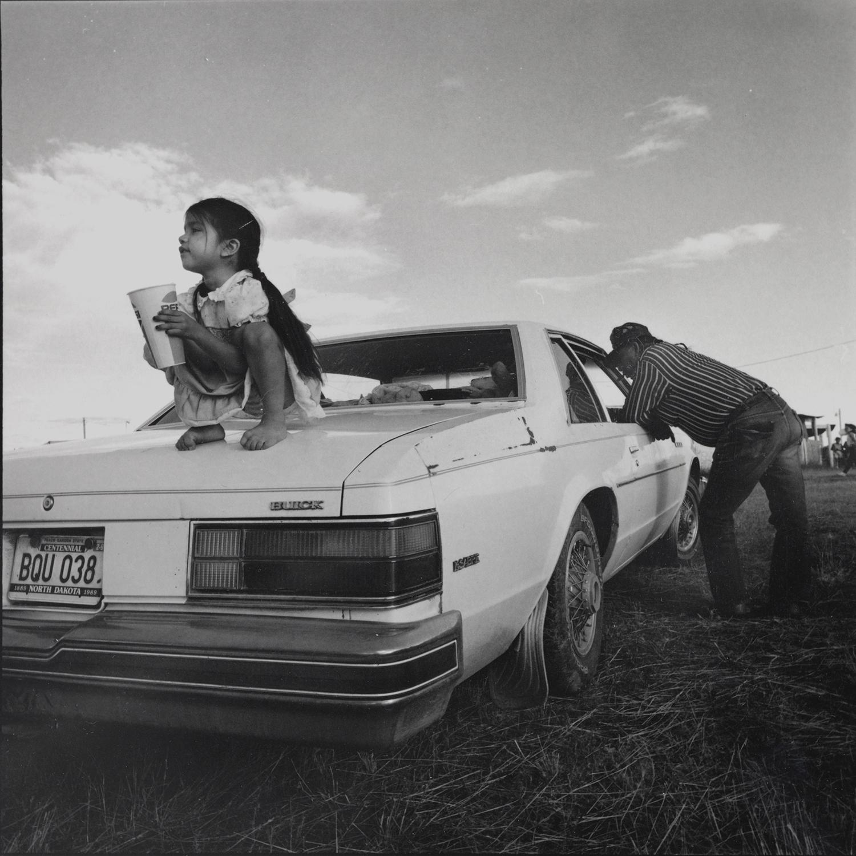 Girl on Car at Pow Wow, Mandaree, NorthDakota, archival pigment print,16x20, 1990