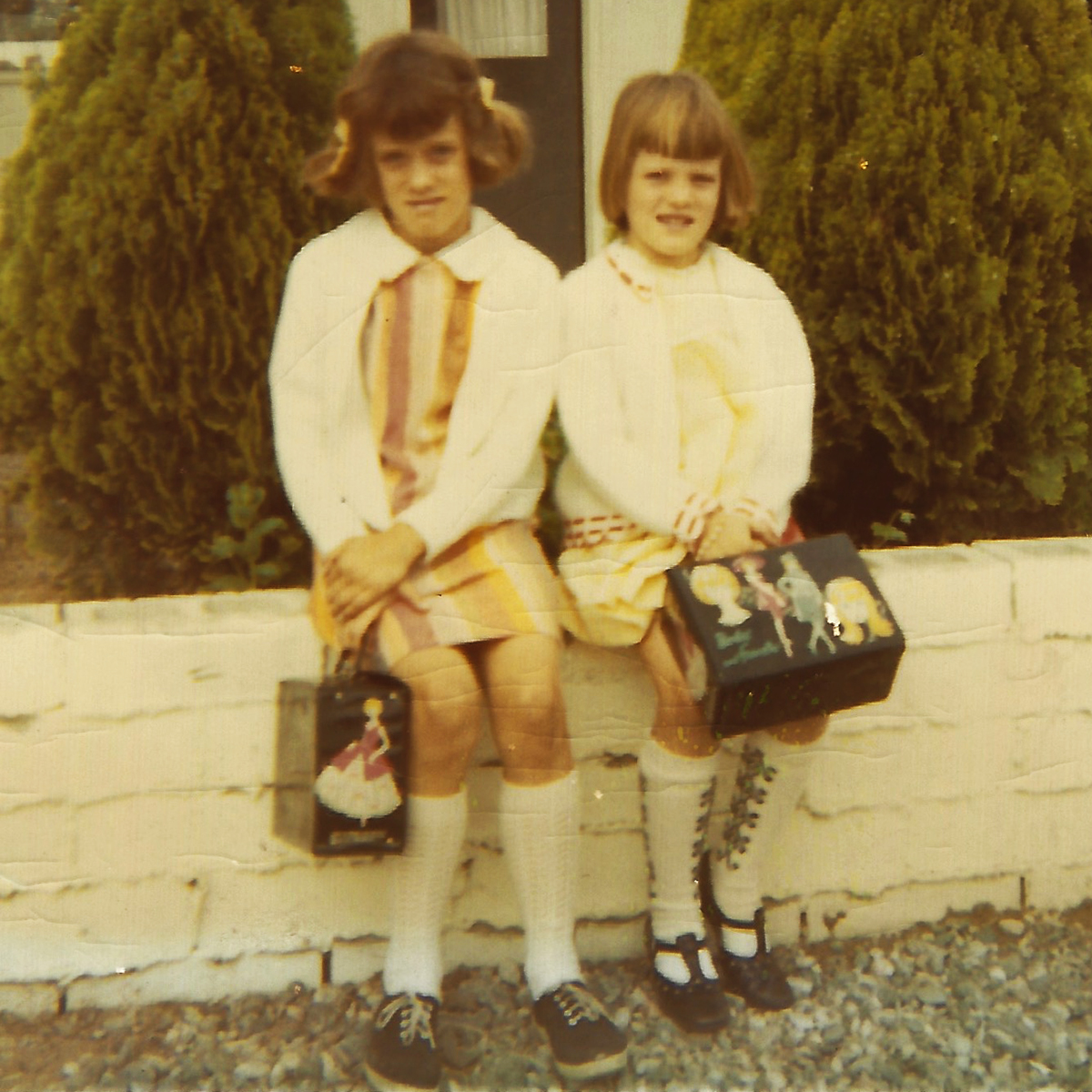 My sister and I with our vinyl-sided lunch boxes; inside the food was wrapped in wax paper