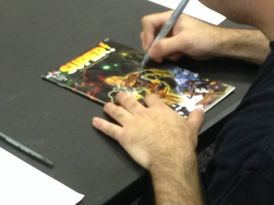 Zack signing the first issue of  Super!