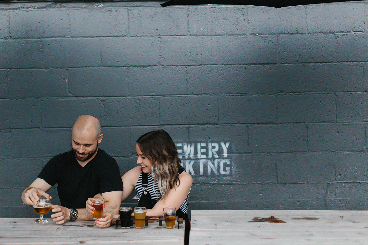 downtown-toronto-in-home-engagement-session-toronto-wedding-photographer-ryanne-hollies-photography-documentary-candid-natural-photos-engaged-in-toronto-brewery-engagement-photos-fun-enjoyable-unique-couple-laughing.jpg