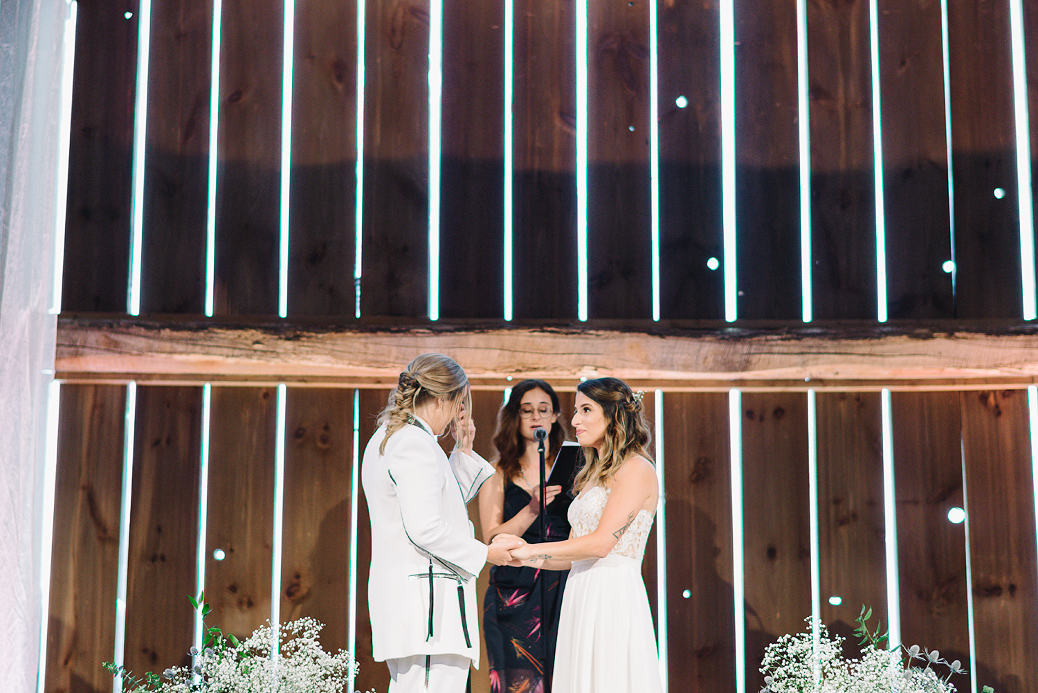 cambium-farms-wedding-ryanne-hollies-photography-gay-wedding-lgbtq-trendy-cool-badass-junebug-weddings-inspiration-ceremony-in-old-barn-bride-and-bride-vows-crying-reaction-other-bride.jpg