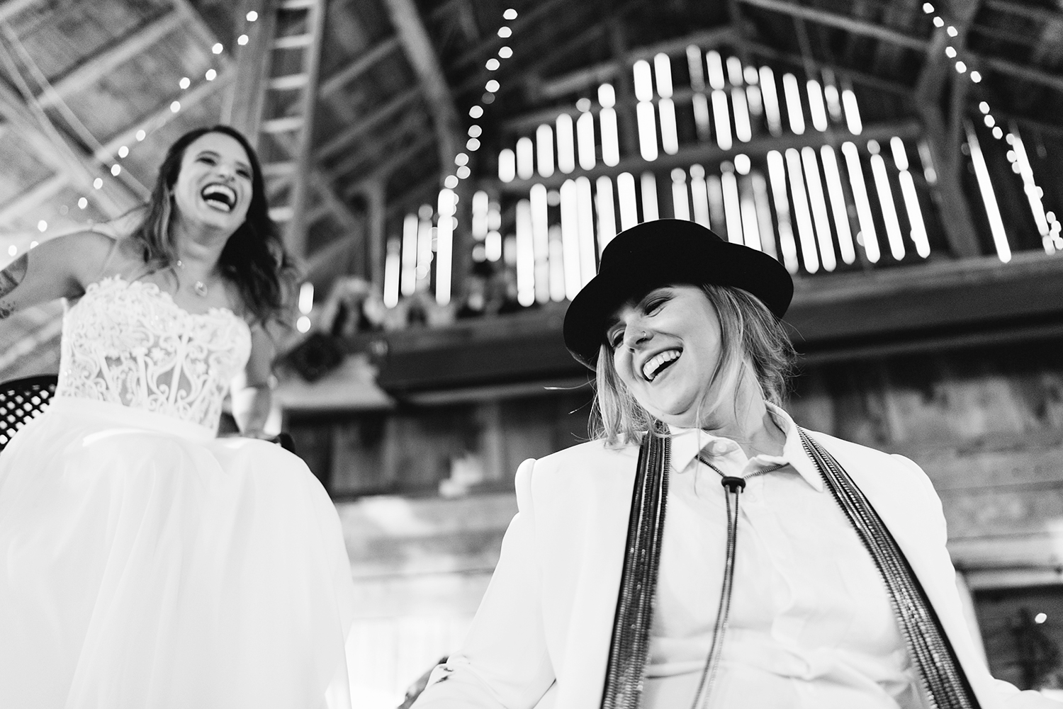 cambium-farms-wedding-ryanne-hollies-photography-gay-wedding-lgbtq-trendy-cool-badass-junebug-weddings-inspiration-cocktail-hour-bride-and-bride-entering-reception-celebration-horah-jewish-tradition-bride-lifted-up-in-chairs.jpg