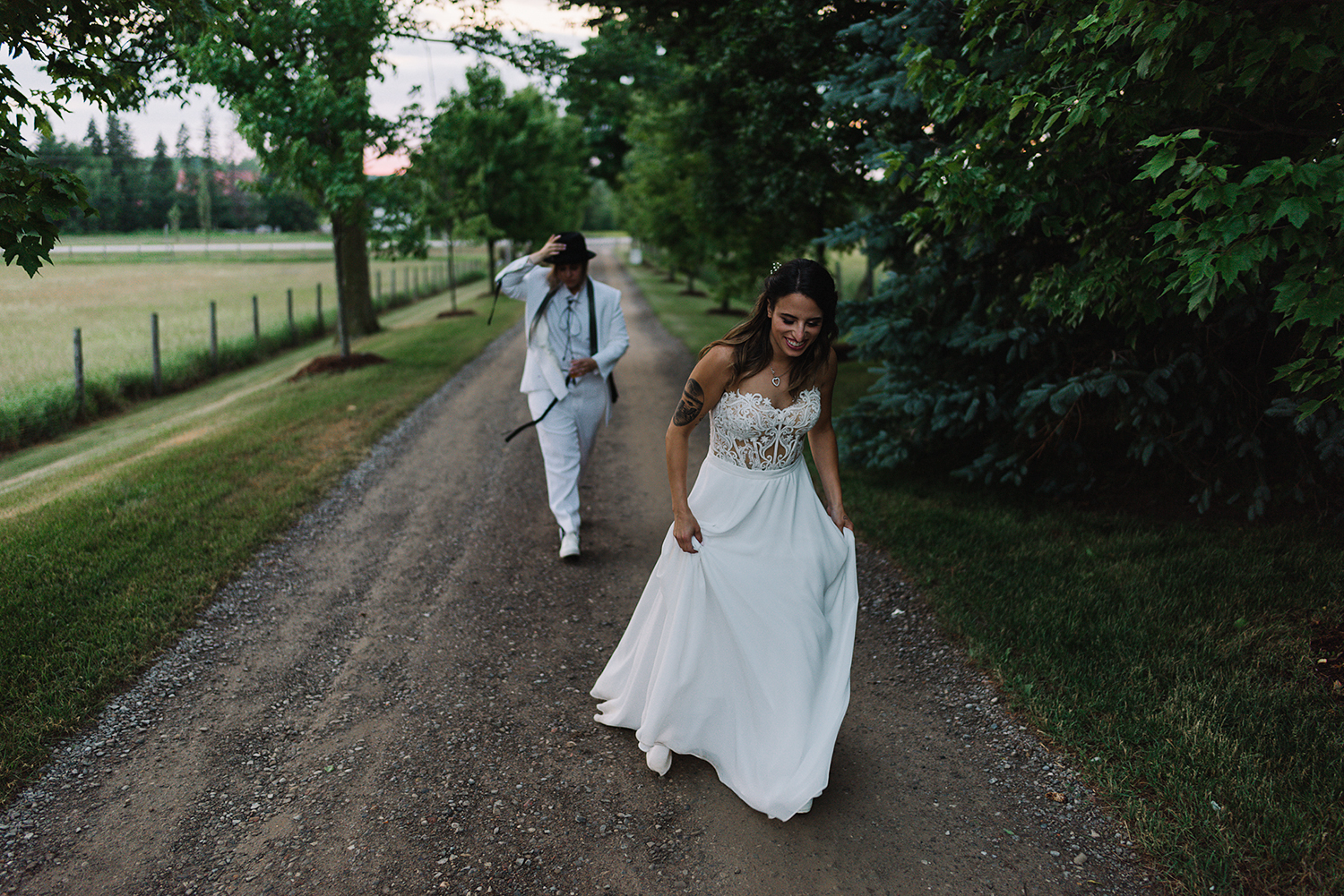 cambium-farms-wedding-ryanne-hollies-photography-gay-wedding-lgbtq-trendy-cool-badass-junebug-weddings-inspiration-wedding-reception-in-a-barn-portraits-at-sunset-bride-and-bride-fence-romantic-moody-sunset-golden-hour-walking.jpg