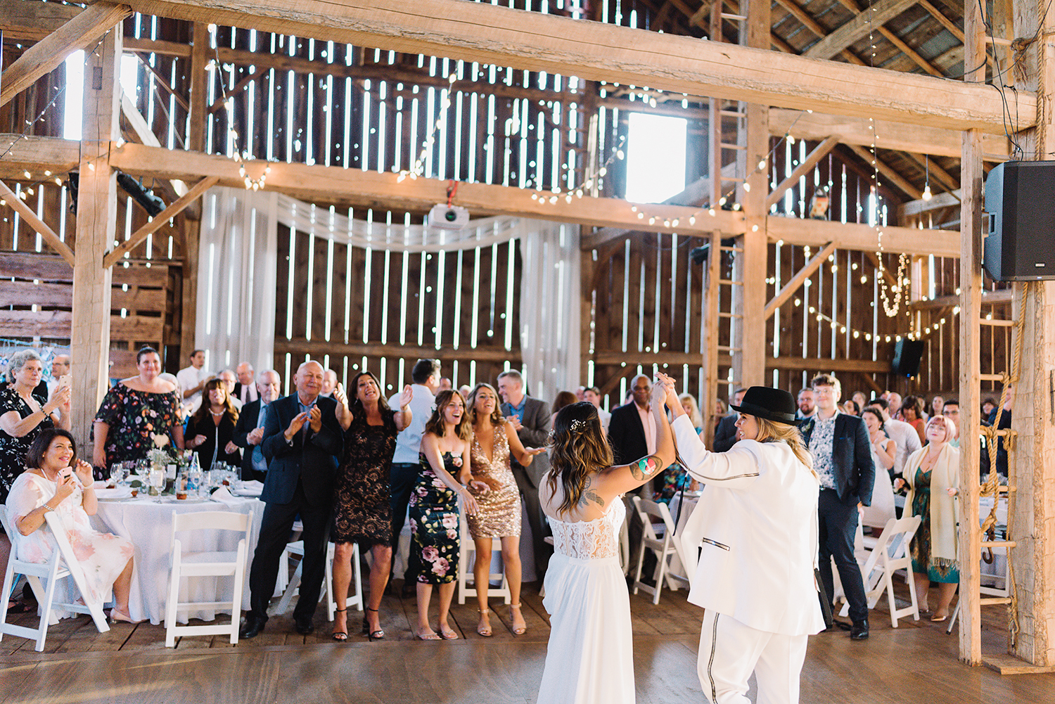 cambium-farms-wedding-ryanne-hollies-photography-gay-wedding-lgbtq-trendy-cool-badass-junebug-weddings-inspiration-cocktail-hour-bride-and-bride-entering-reception-celebration-cheering.jpg