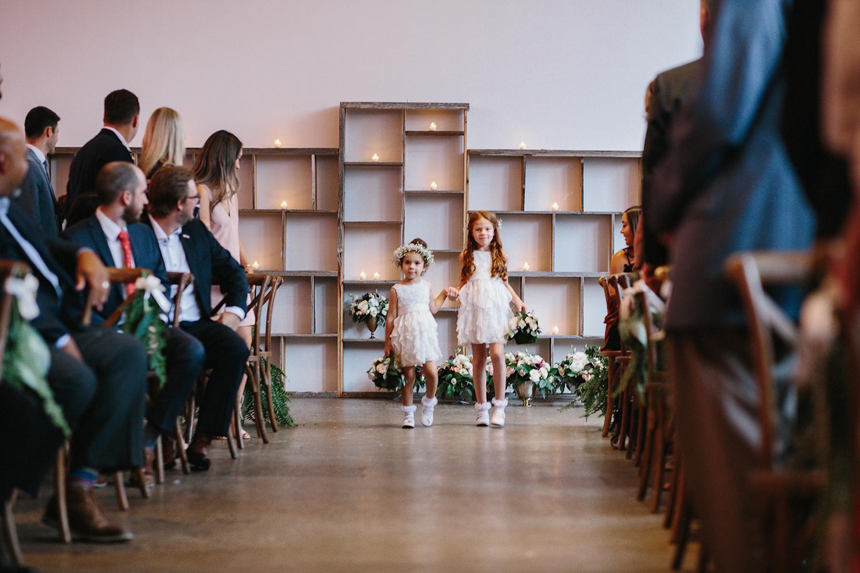 downtown-toronto-wedding-photographer-ryanne-hollies-photography-airship37-distillery-district-wedding-day-modern-minimalist-venues-in-toronto-ceremony-cute-flower-girls-walking-down-the-aisle.jpg