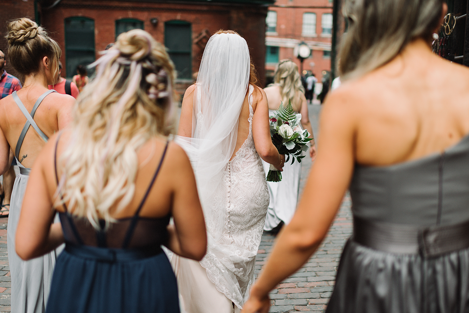 torontos-best-documentary-wedding-photographers-ryanne-hollies-photography-fine-art-photojournalism-artistic-moody-toronto-airship37-distillery-district-groom-and-bride-portraits-candid-bridal-party-walking-together.jpg