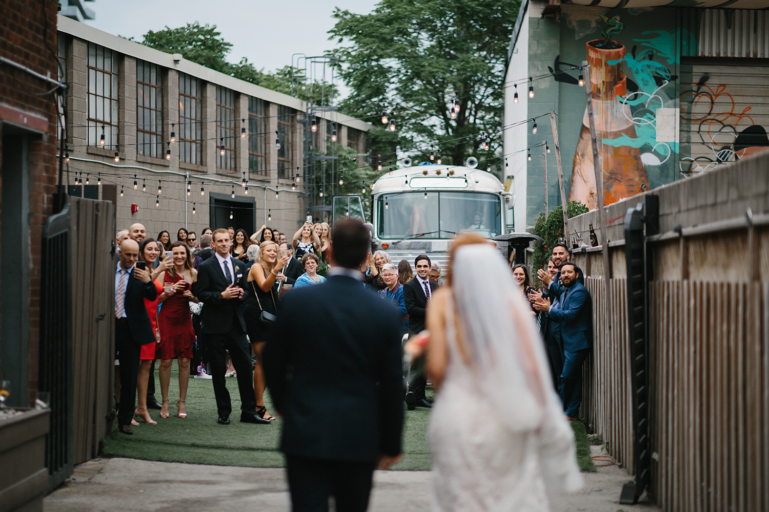 torontos-best-wedding-photographers-ryanne-hollies-photography-photojournalism-artistic-moody-toronto-airship37-graffiti-editorial-cocktail-hour-guests-cheering-for-bride-and-groom.jpg