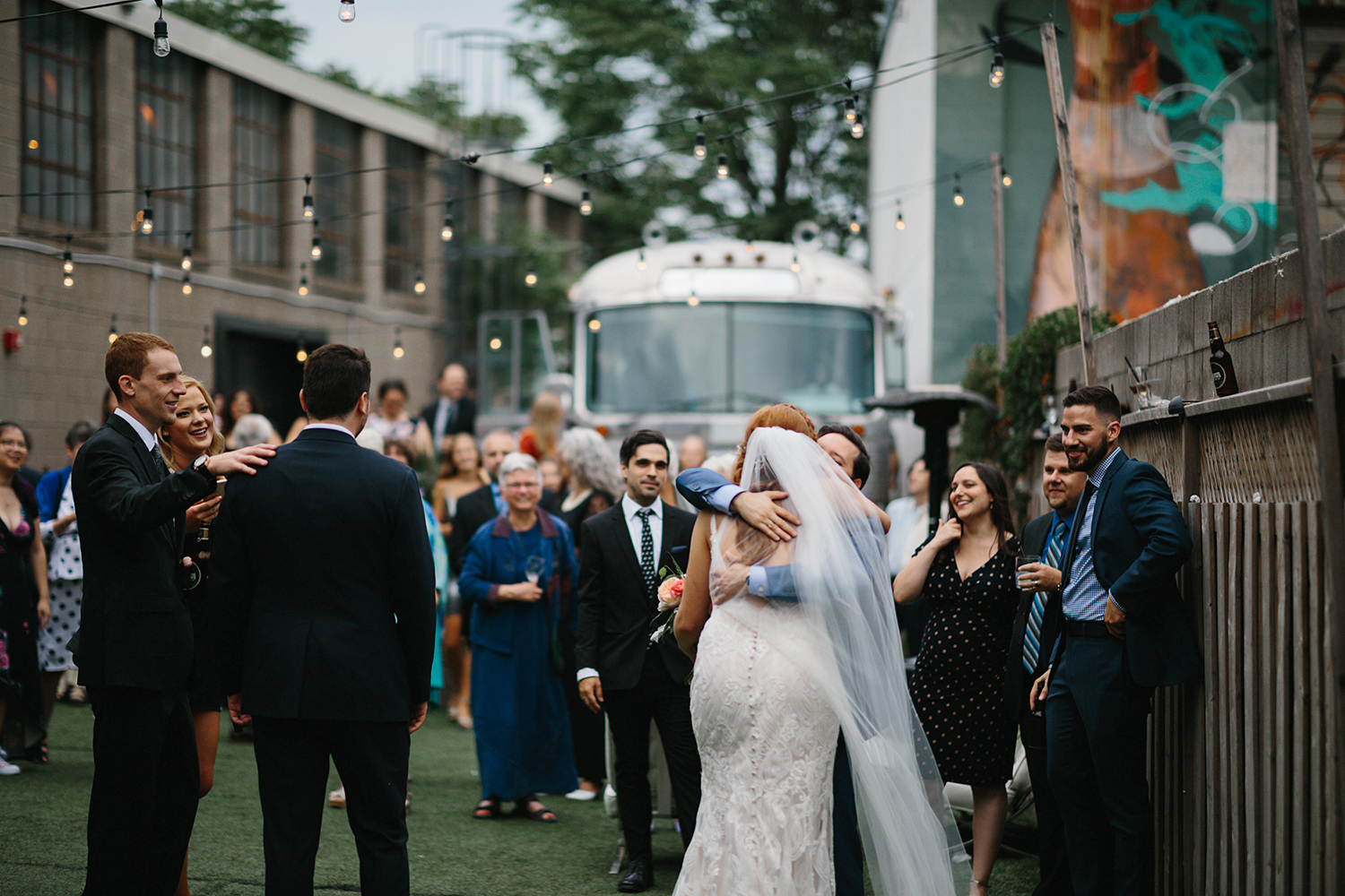 torontos-best-wedding-photographers-ryanne-hollies-photography-photojournalism-artistic-moody-toronto-airship37-graffiti-editorial-cocktail-hour-guests-cheering-for-bride-and-groom-hugs.jpg