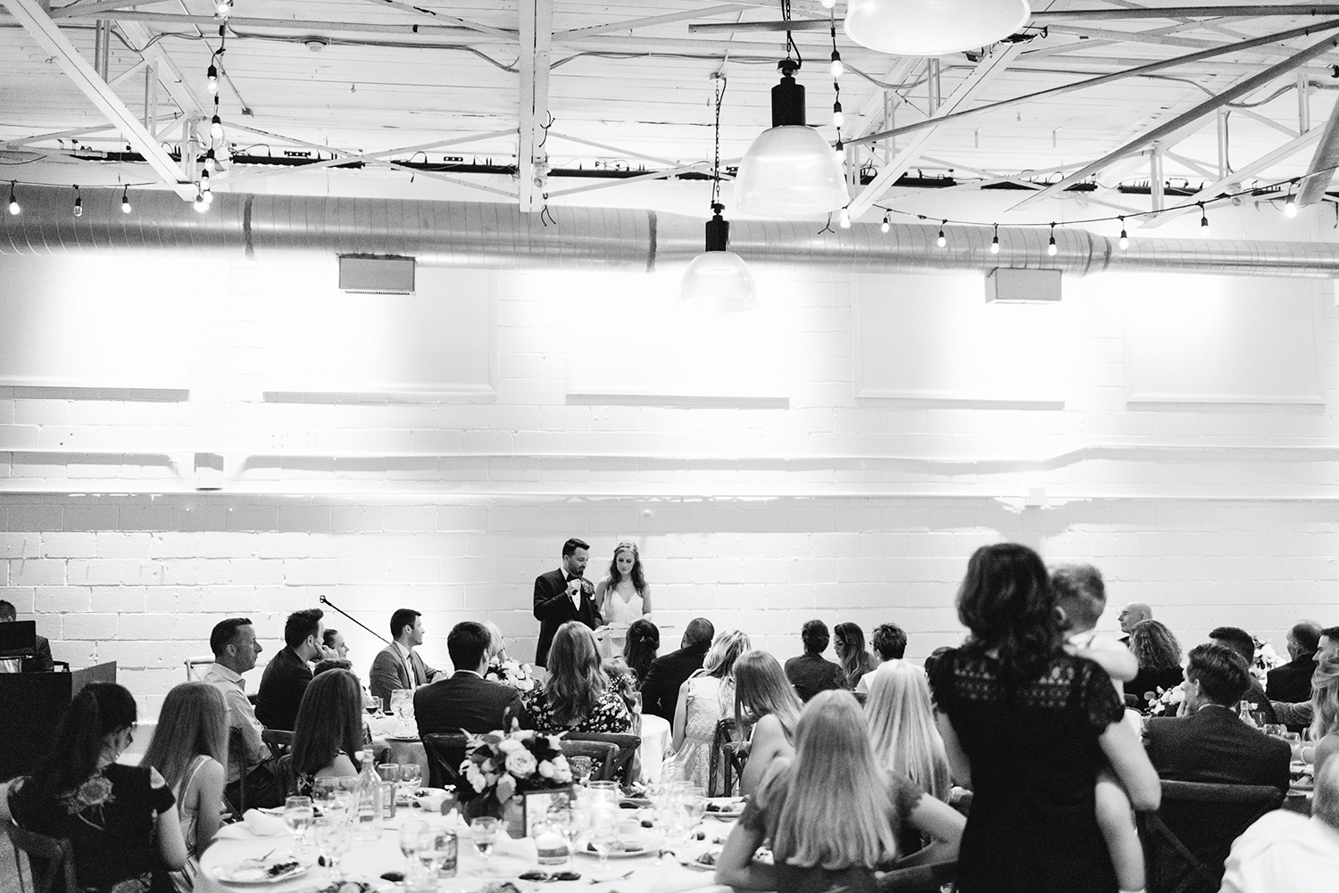 torontos-best-wedding-photographers-ryanne-hollies-photography-photojournalism-artistic-moody-toronto-airship37-graffiti-editorial-reception-bride-and-groom-speech-cheers-grooms-speech-to-wife-honest-emotional-sincere-whole-room.jpg