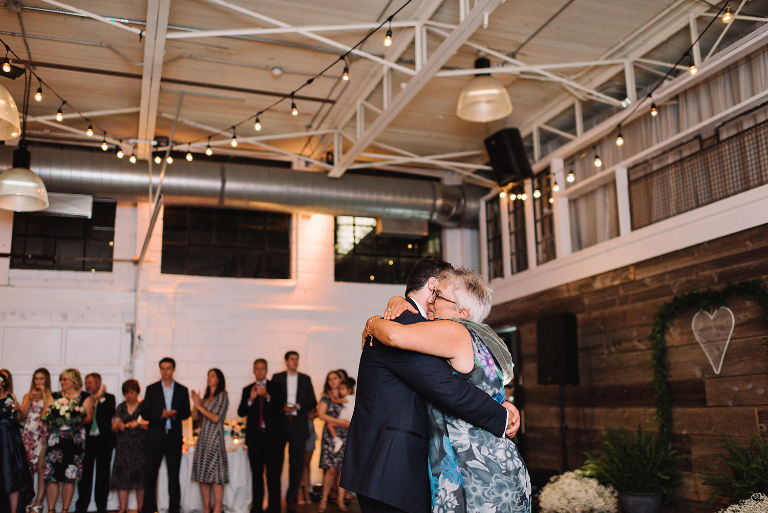 torontos-best-wedding-photographers-ryanne-hollies-photography-photojournalism-artistic-moody-toronto-airship37-graffiti-editorial-reception-mother-son-dance-with-groom-so-cute-hugging.jpg
