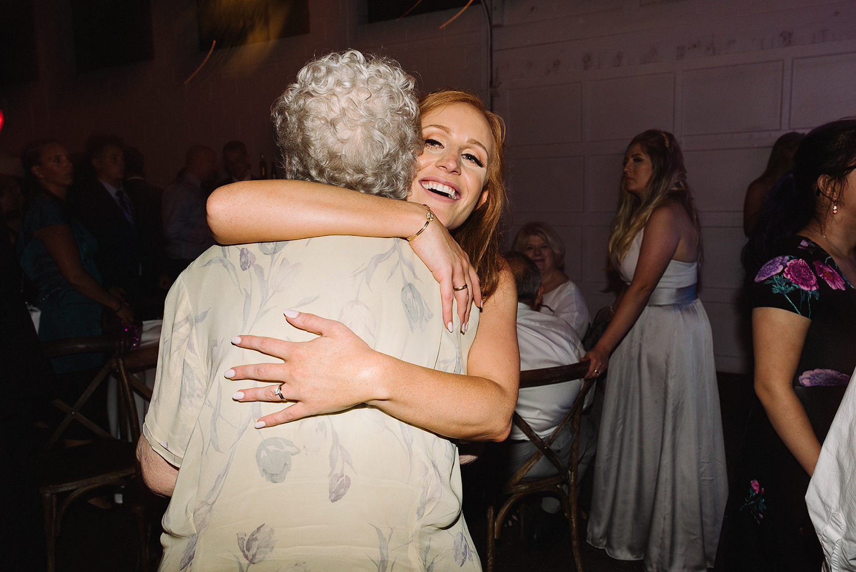 torontos-best-wedding-photographers-ryanne-hollies-photography-photojournalism-artistic-moody-toronto-airship37-graffiti-editorial-reception-dancing-together-hilarious-good-times-memories-grandma-hugging-bride.jpg