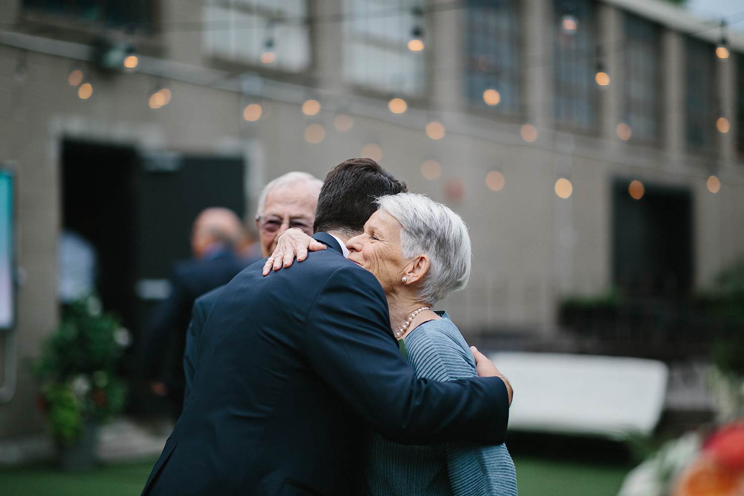 torontos-best-documentary-wedding-photographers-ryanne-hollies-photography-fine-art-photojournalism-artistic-moody-creative-inspiration-downtown-toronto-airship37-venue-modern-hipster-cocktail-hour-groom-hugging-his-new-grandma.jpg