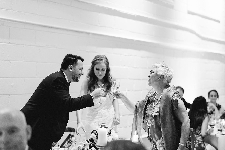 torontos-best-wedding-photographers-ryanne-hollies-photography-photojournalism-artistic-moody-toronto-airship37-graffiti-editorial-reception-bride-and-groom-speech-cheers-with-mom.jpg