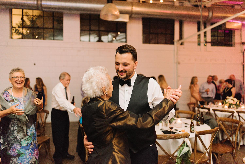 torontos-best-wedding-photographers-ryanne-hollies-photography-photojournalism-artistic-moody-toronto-airship37-graffiti-editorial-reception-dancing-together-hilarious-good-times-memories-dancing-partying-photos-grandmas-hugging-groom.jpg