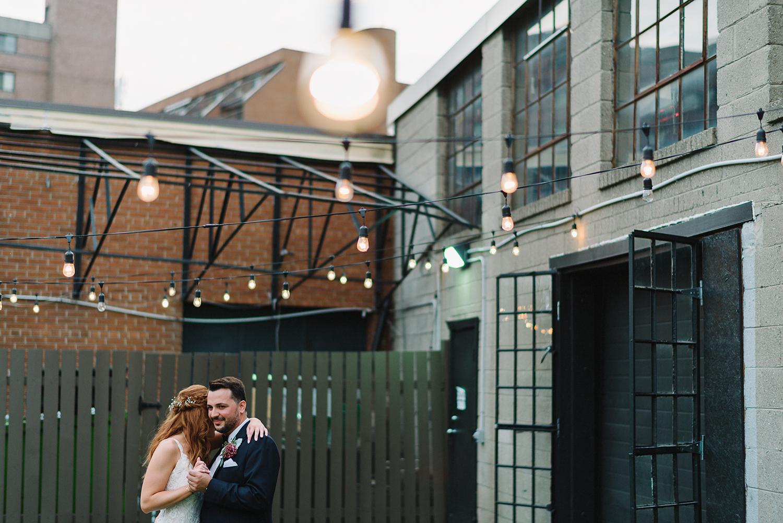 torontos-best-wedding-photographers-ryanne-hollies-photography-photojournalism-artistic-moody-toronto-airship37-graffiti-editorial-reception-outdoor-details-sunset-urban-string-lights-first-dance.jpg
