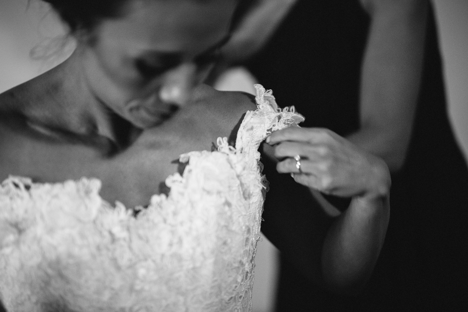 muskoka-wedding-photographer-toronto-wedding-photography-hidden-valley-resort-documentary-photojournalistic-fine-art-wedding-photography-getting-ready-bride-putting-on-lace-vintage-wedding-dress-with-bridesmaid-bw.jpg