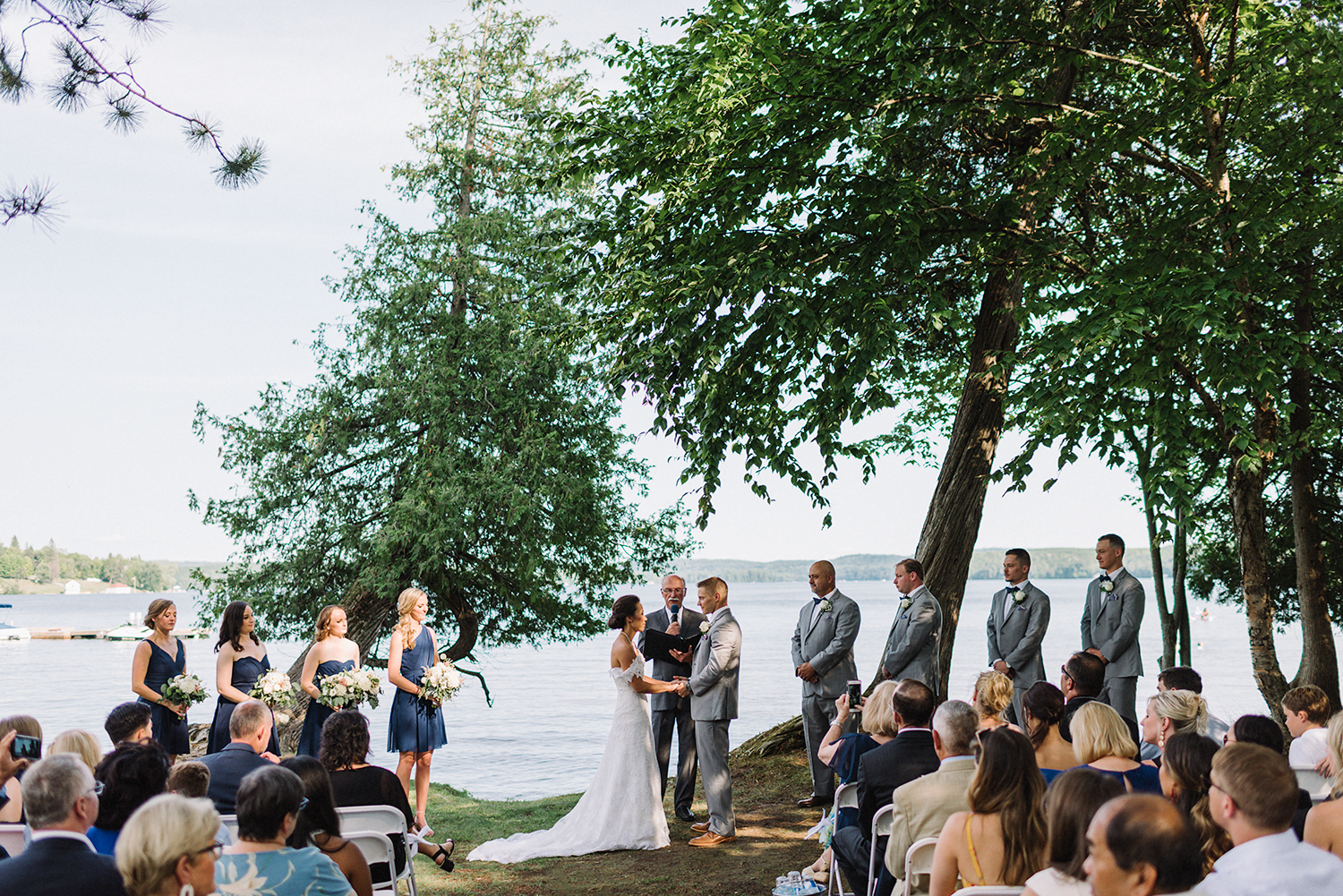 toronto-wedding-photographers-hidden-valley-resort-ryanne-hollies-photography-documentary-photojournalistic-fine-art-wedding-photography-lakeside-ceremony-cottage-country-bride-and-groom-saying-vows-bride-emotional-groom-and-all-guests.jpg