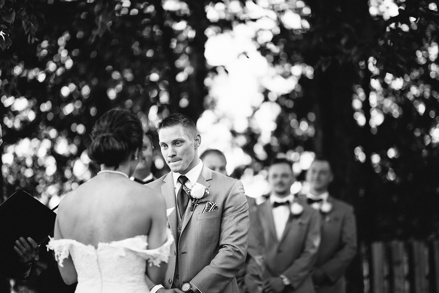 muskoka-wedding-photographer-toronto-wedding-photography-hidden-valley-resort-documentary-photojournalistic-fine-art-wedding-photography-lakeside-ceremony-cottage-country-bride-and-groom-saying-vows-bride-emotional-groom-crying-bw.jpg