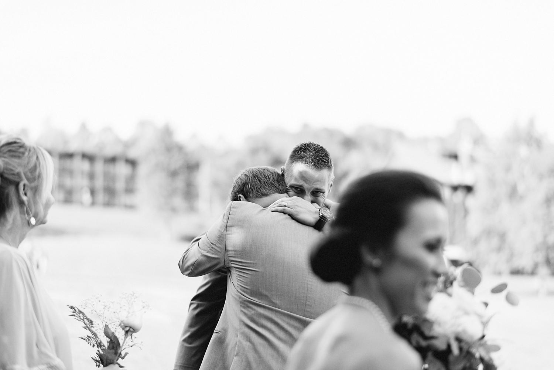 muskoka-wedding-photographer-hidden-valley-resort-film-photography-junebug-weddings-inspiration-wedding-decoration-ideas-cocktail-hour-groom-hugging-brother.jpg