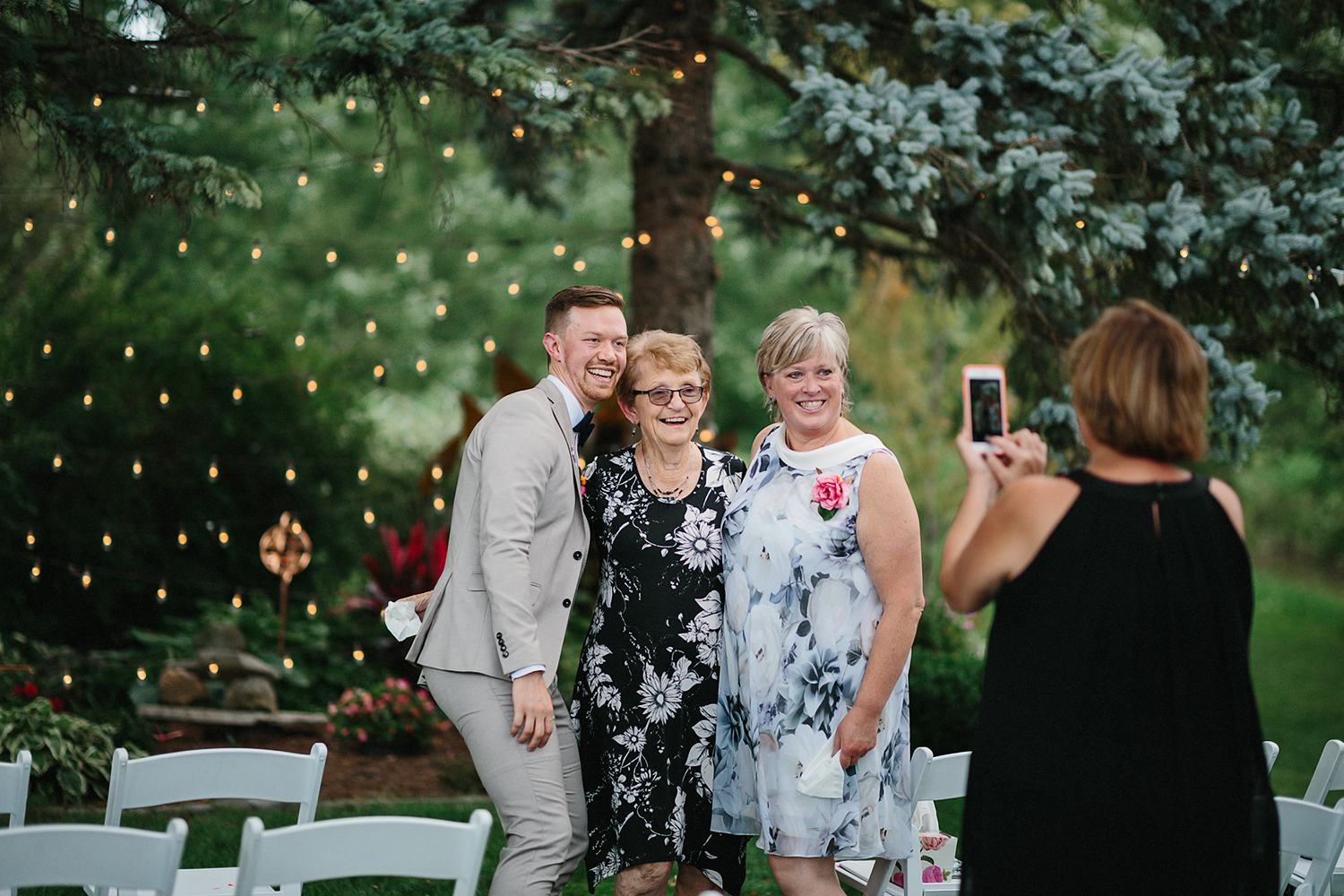 Backyard-family-intimate-cottage-wedding-chatum-kent-toronto-ontario-film-photographer-ryanne-hollies-photography-diy-string-lights-and-lanterns-reception-dinner-candid-moments-groom-grandma-mom-photobomb.jpg