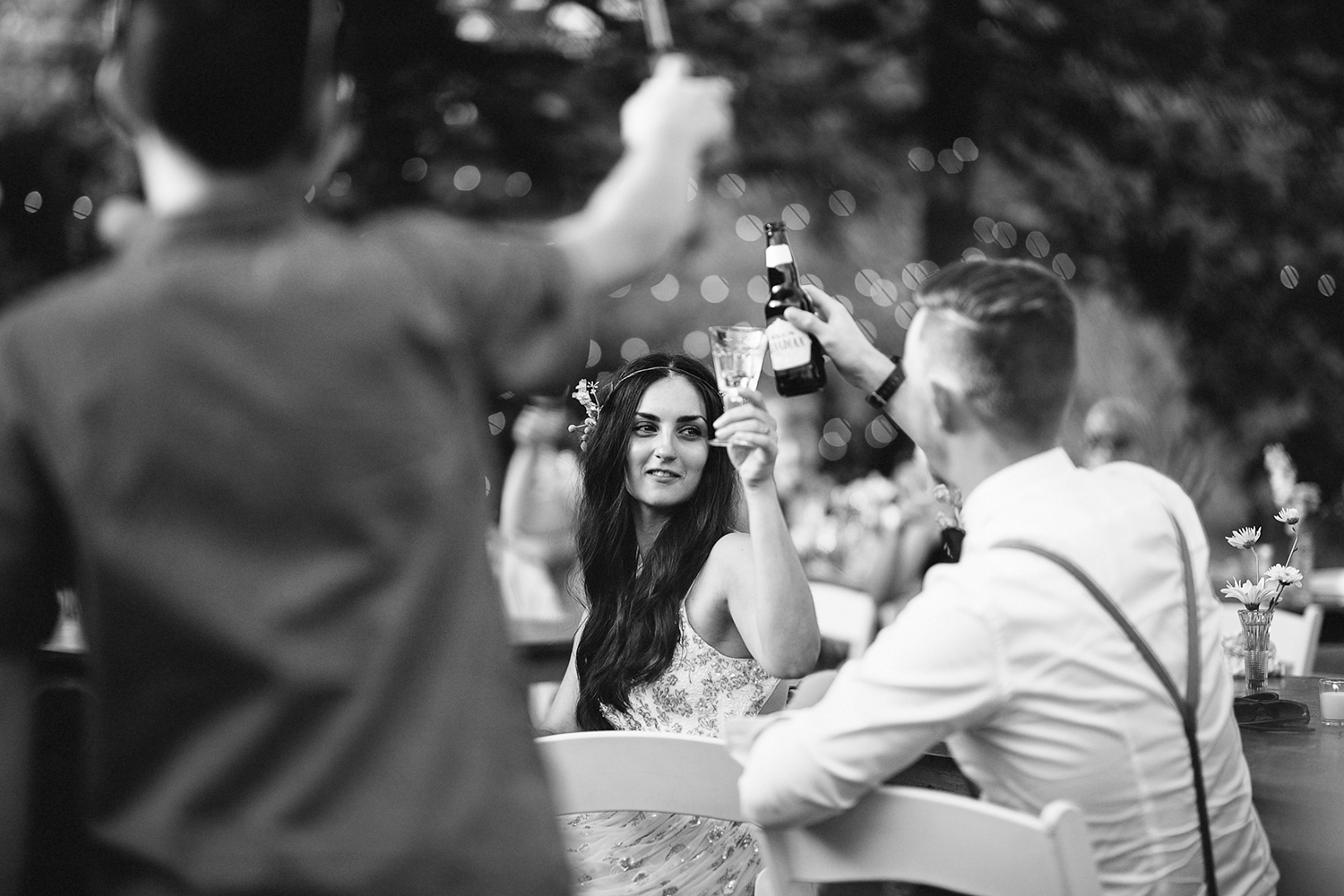 Backyard-toronto-film-photographer-ryanne-hollies-photography-diy-string-lights-and-lanterns-reception-dinner-documentary-wooden-harvest-tables-diy-decor-speeches-bride-and-groom-siblings-speech-groom-crying-candid-cheers-drinks-bw.jpg