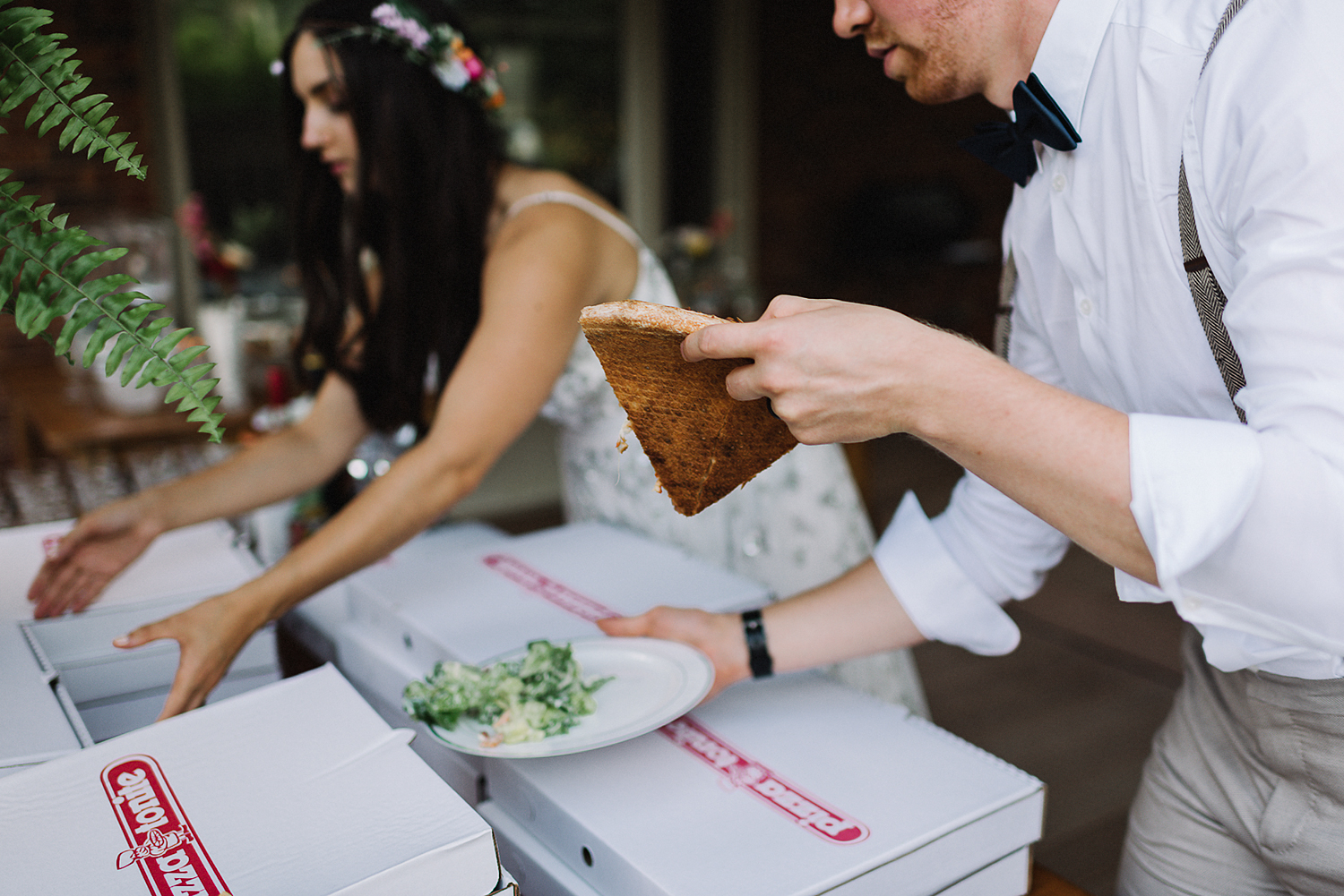 Backyard-toronto-film-photographer-ryanne-hollies-photography-diy-string-lights-and-lanterns-reception-dinner-documentary-wooden-harvest-tables-diy-decor-speeches-bride-and-groom-eating-pizza.jpg
