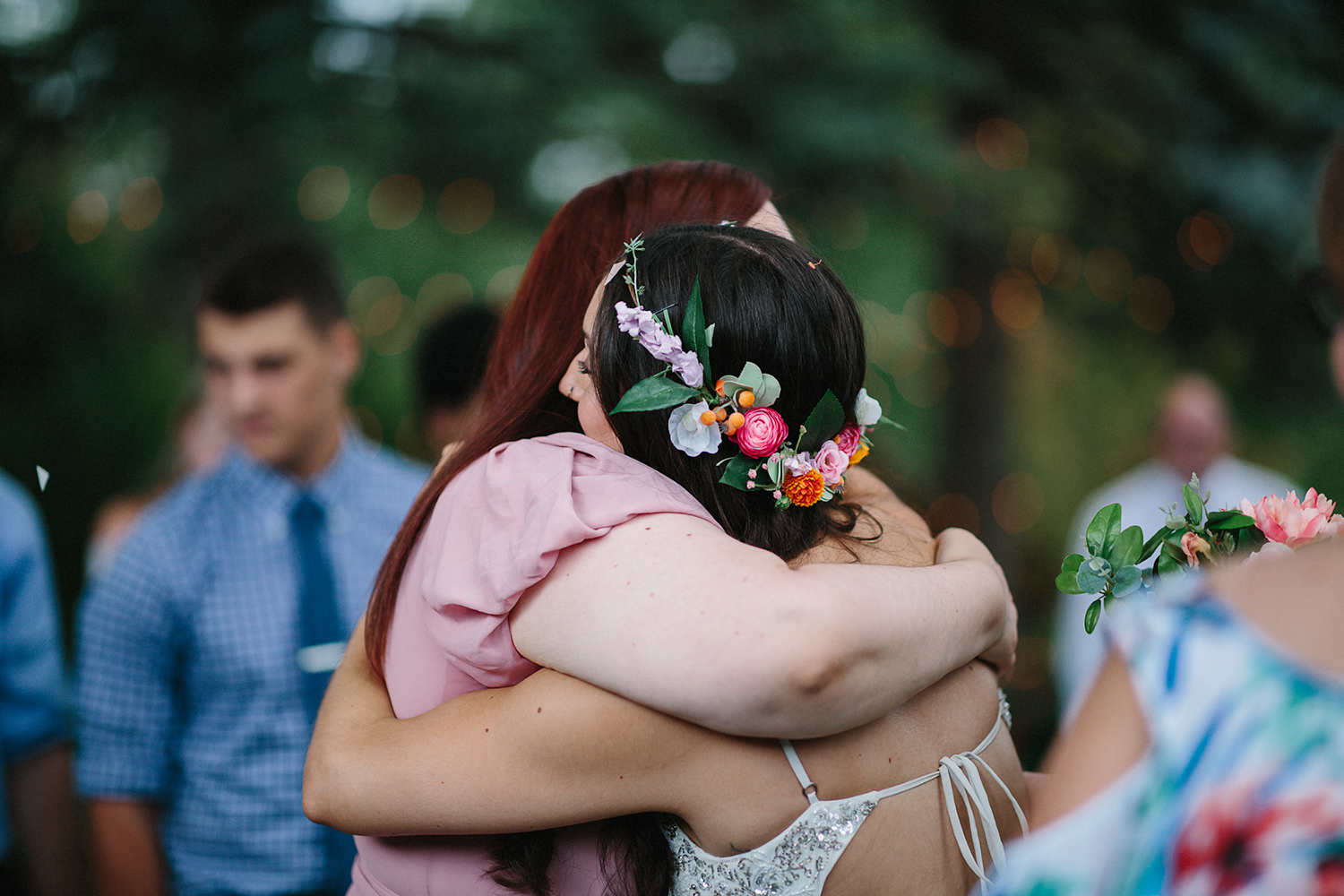 Backyard-family-intimate-cottage-wedding-chatum-kent-toronto-ontario-film-photographer-ryanne-hollies-photography-diy-string-lights-and-lanterns-reception-dinner-bride-and-groom-hugging-sister-emotional-candid-moments.jpg