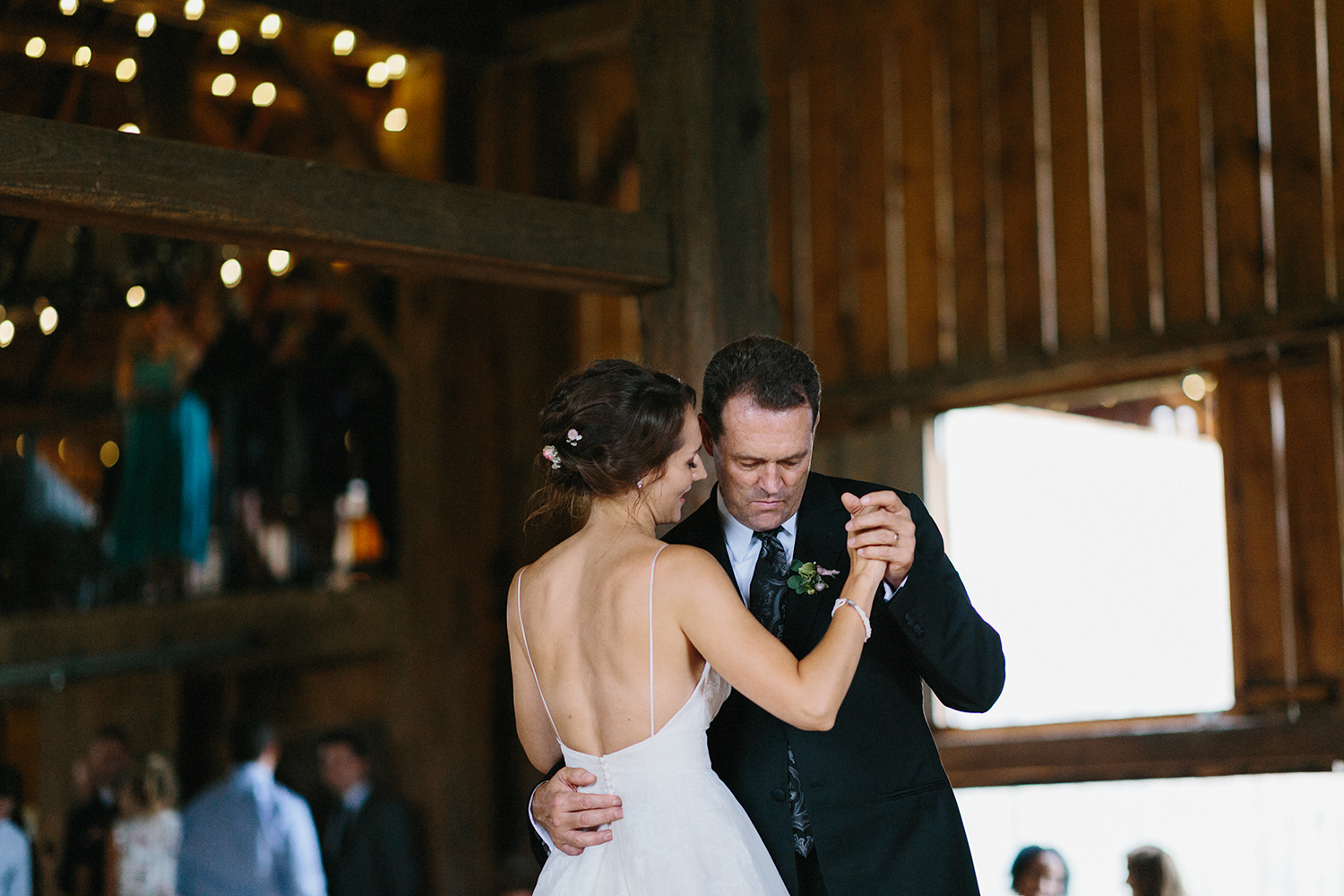cambium-farms-wedding-ryanne-hollies-photography-gay-wedding-lgbtq-trendy-cool-badass-junebug-weddings-inspiration-reception-celebration-bride-and-bride-first-dance-in-barn-with-string-lights-and-other-guests-dancing.jpg