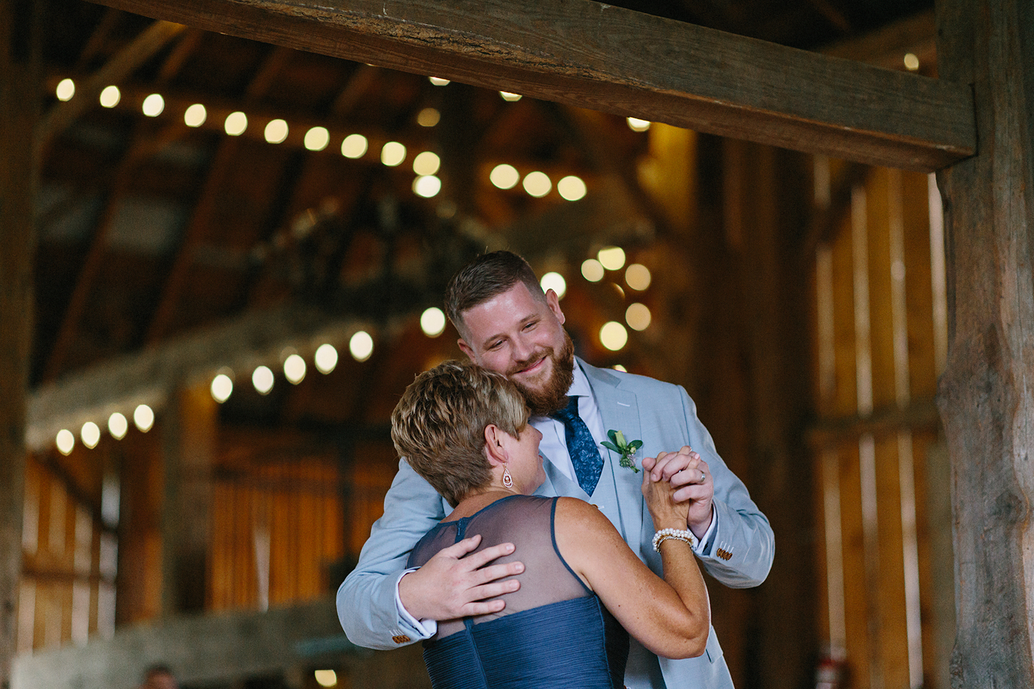 cambium-farms-wedding-ryanne-hollies-photography-gay-wedding-lgbtq-trendy-cool-badass-junebug-weddings-inspiration-reception-celebration-bride-and-bride-first-dance-in-barn-with-string-lights-and-other-guests-around-them-in-love-pride-2018.jpg