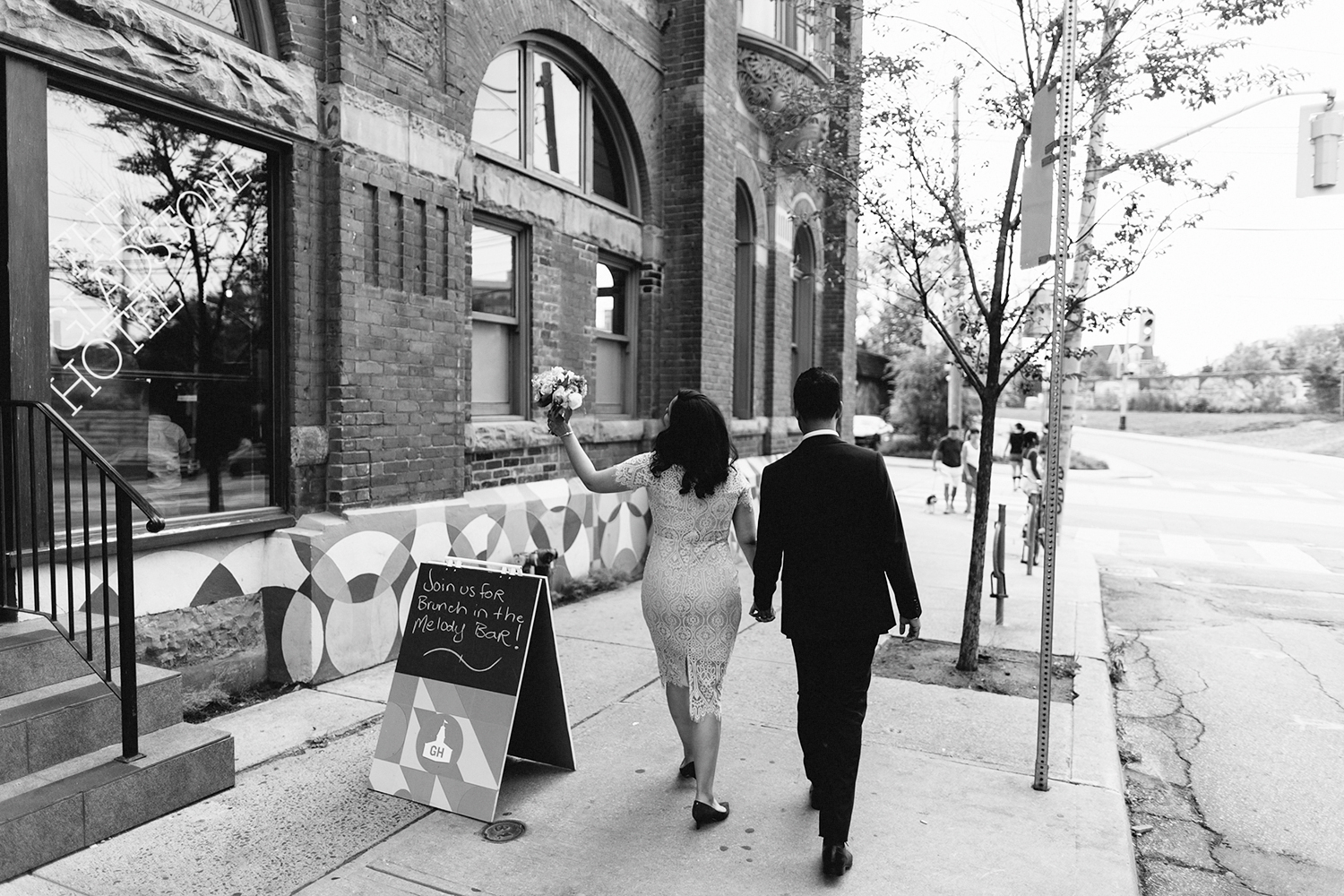 Best-Wedding-Photographers-in-Toronto-Downtown-Urban-Gladstone-Hotel-Venue-Inspiration-Top-Venues-in-Toronto-boutique-hotel-candid-documentary-brunch-wedding-couples-portraits-walking-together-inbetween-moments-bride-waving.jpg