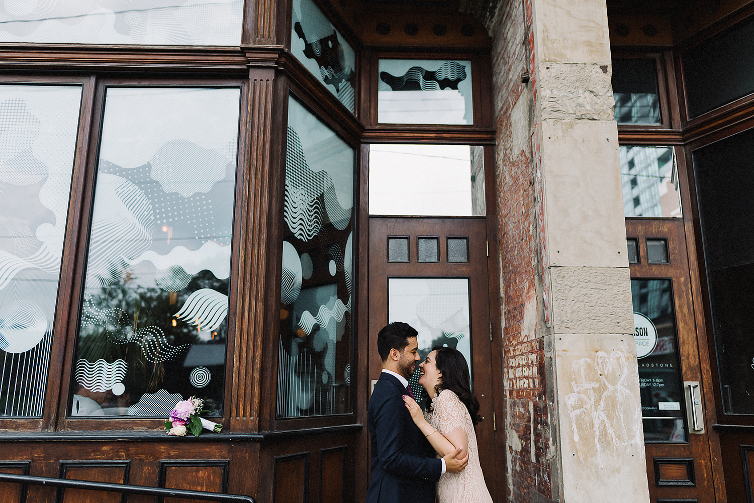 Minimalist-Wedding-at-Gladstone-Hotel-Best-Wedding-Photogrpahers-in-Toronto-with-Documentary-and-Editorial-Style-Ryanne-Hollies-Floral-Bouquet-and-Wedding-Dress-Detail-Portraits-along-queent-street-west-Groom-Portrait-candid-laughing.jpg