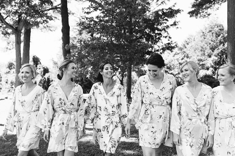 Bride-and-bridesmaids-in-floral-robes-walking-At-Egaridge-Resort-Venue-Muskoka-Ontario.jpg