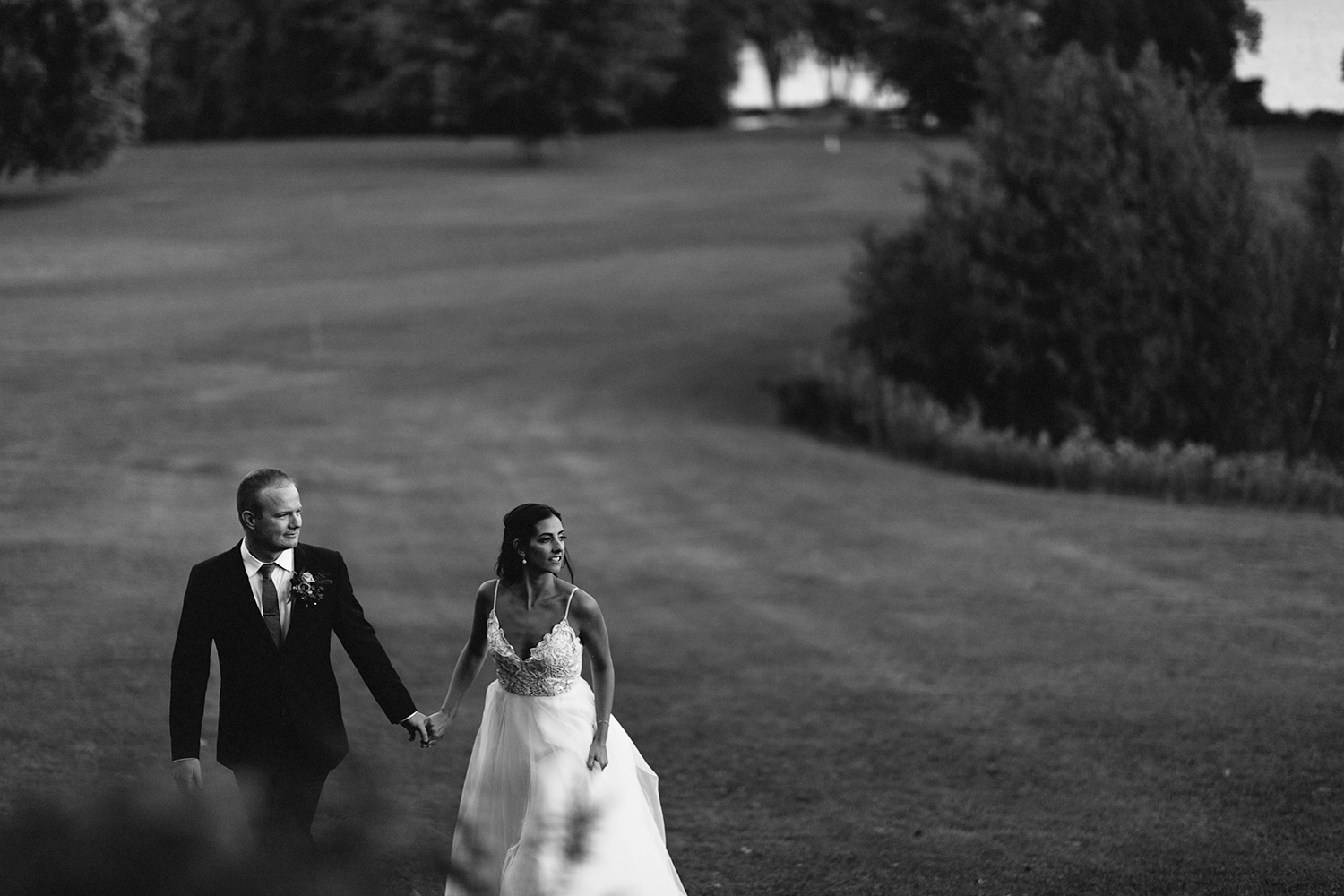 bw-couples-portrait-ideas-sunset-golden-hour-in-field-view-of-lake-pink-sky-At-Eganridge-Resort-Venue-Muskoka-Ontario-Wedding-Photography-by-Ryanne-Hollies-Photography-Toronto-Documentary-Wedding-Photographer.jpg
