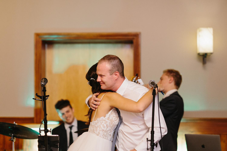 bride-and-groom-speech-hug-reception-At-Eganridge-Resort-Venue-Muskoka-Ontario-Wedding-Photography-by-Ryanne-Hollies-Photography-Toronto-Documentary-Wedding-Photographer.jpg