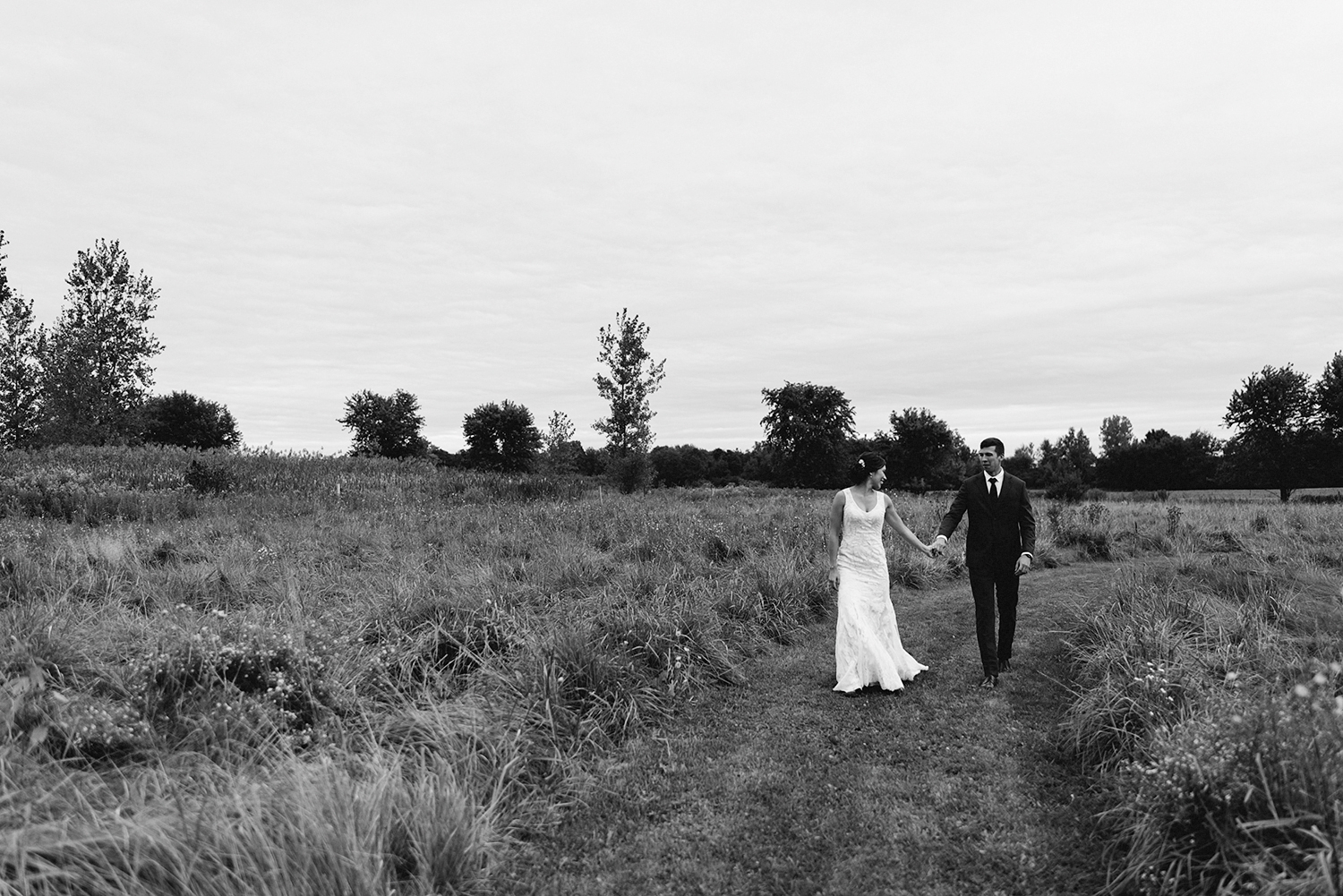 editorial-bride-and-groom-walking-field-wilderness-outdoors-romantic-moody-real-moments-photos-toronto's-best-wedding-photographers-candid-documentary-style-photography-london-ontario-wedding-inspiration.jpg