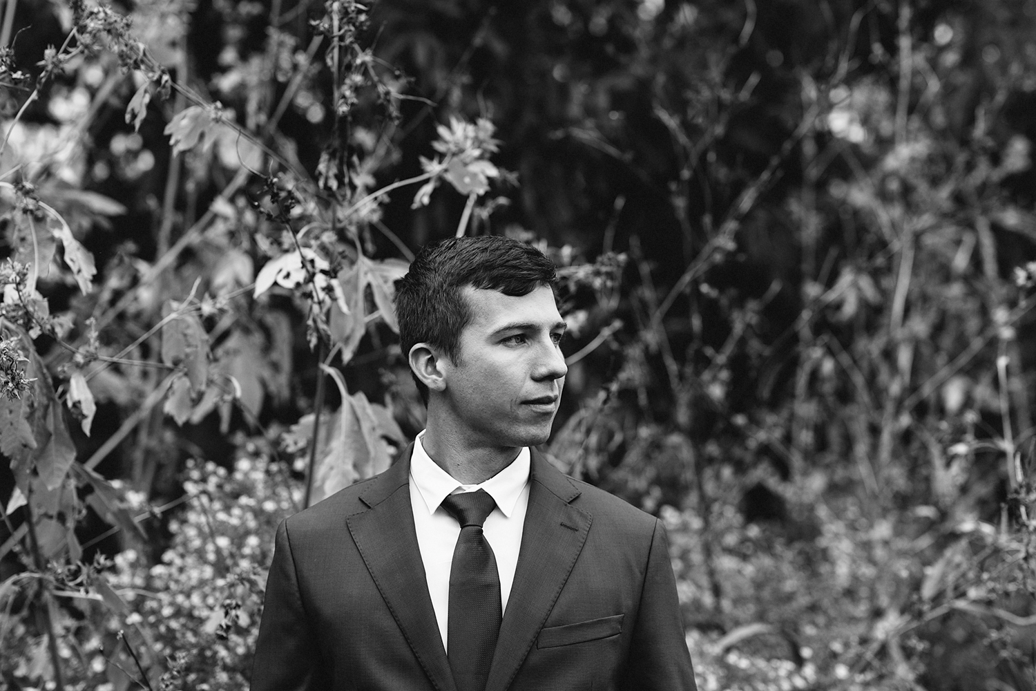 editorial-field-flowers-groom-portrait-moody-real-moments-photos-toronto's-best-wedding-photographers-candid-documentary-style-photography-london-ontario-wedding-inspiration.jpg
