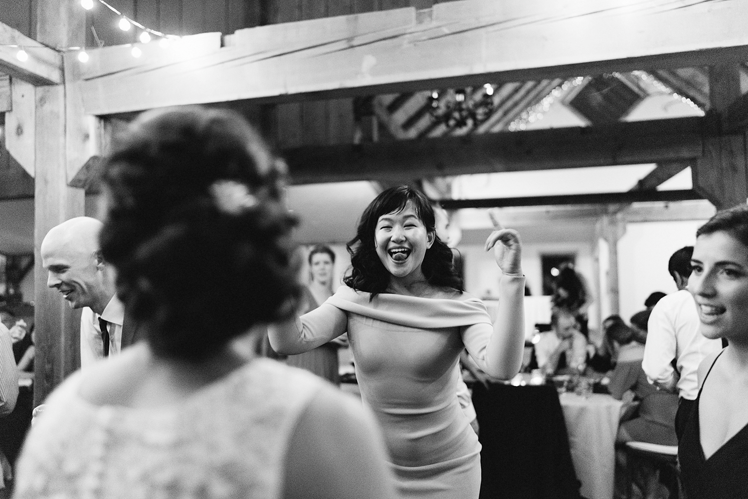 bw-candid-cute-dancing-in-barn-with-string-lights-toronto's-best-analog-documentary-wedding-photographers-candid-photography-london-ontario-wedding-inspiration.jpg