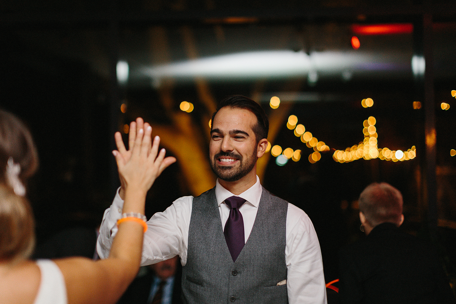 Prince-Edward-County-Wedding-Photographer-Drake-Devonshire-Elopement-Ryanne-Hollies-Photography-junebug-weddings-best-of-the-best-reception-glassbox-groom-high-fiving-bride.jpg